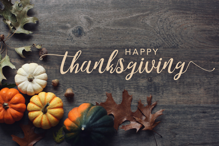 Happy-Thanksgiving-greeting-text-with-pumpkins,-squash-and-leaves-over-dark-wood-background-867771348_726x484.jpeg