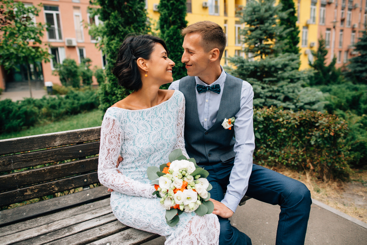 Happy-bride-and-groom-sitting-on-bench-on-wedding-day-912584418_726x484.jpeg
