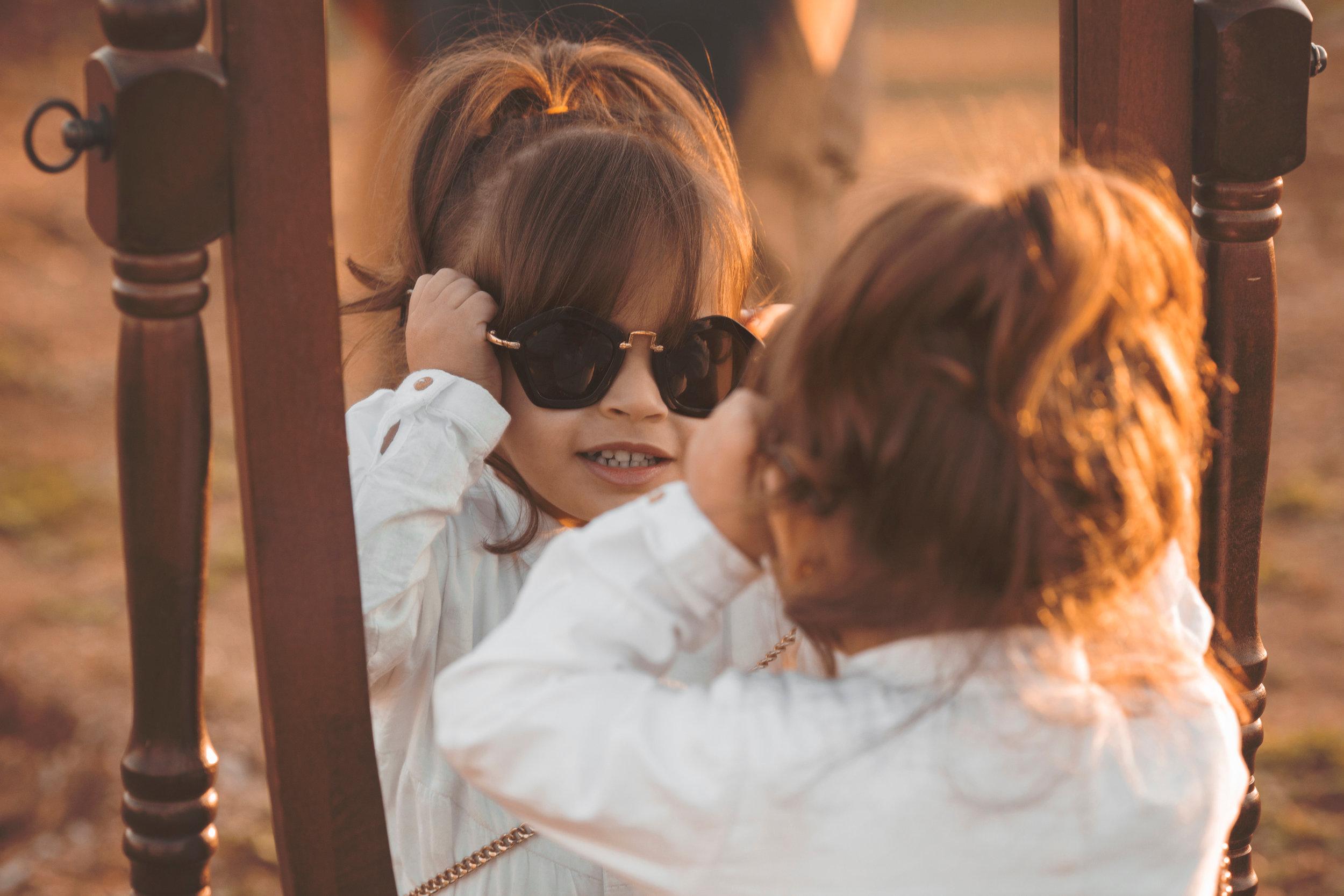 Canva - Girl in White Long-sleeved Shirt Wearing Sunglasses Facing Mirror.jpg