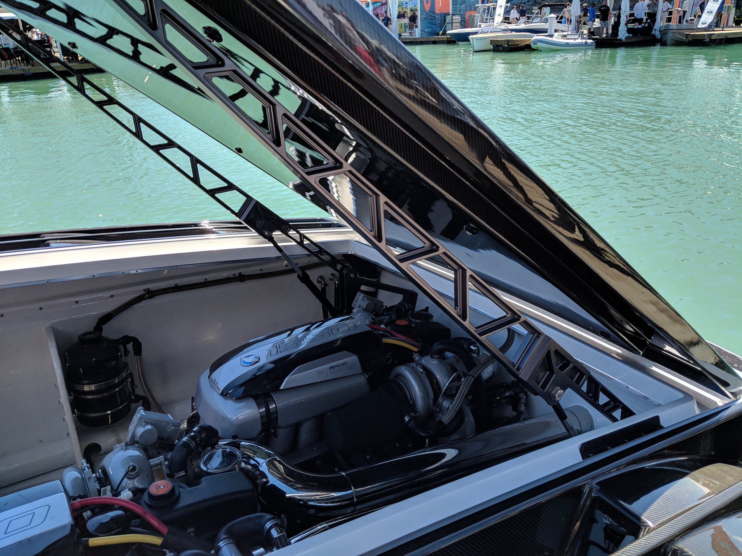"""The beautiful rigging of the twin 1550 Mercury Racing engines. You can see the extra space provided by the wide 9'6"""" beam. Carbon fiber hatch and beautiful hinges that lift the cover."""