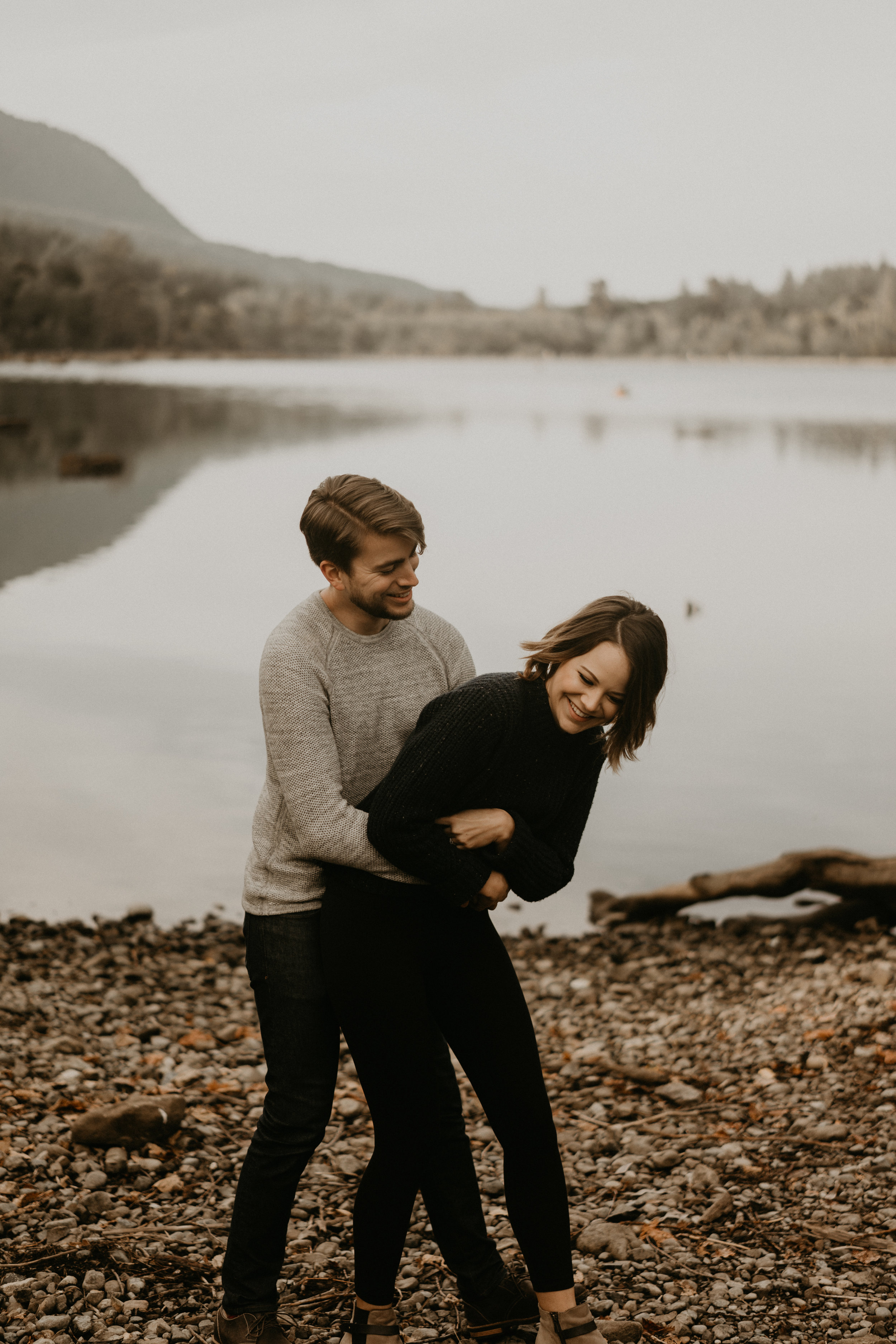couple having fun for their engagement photos by rattlesnake lake