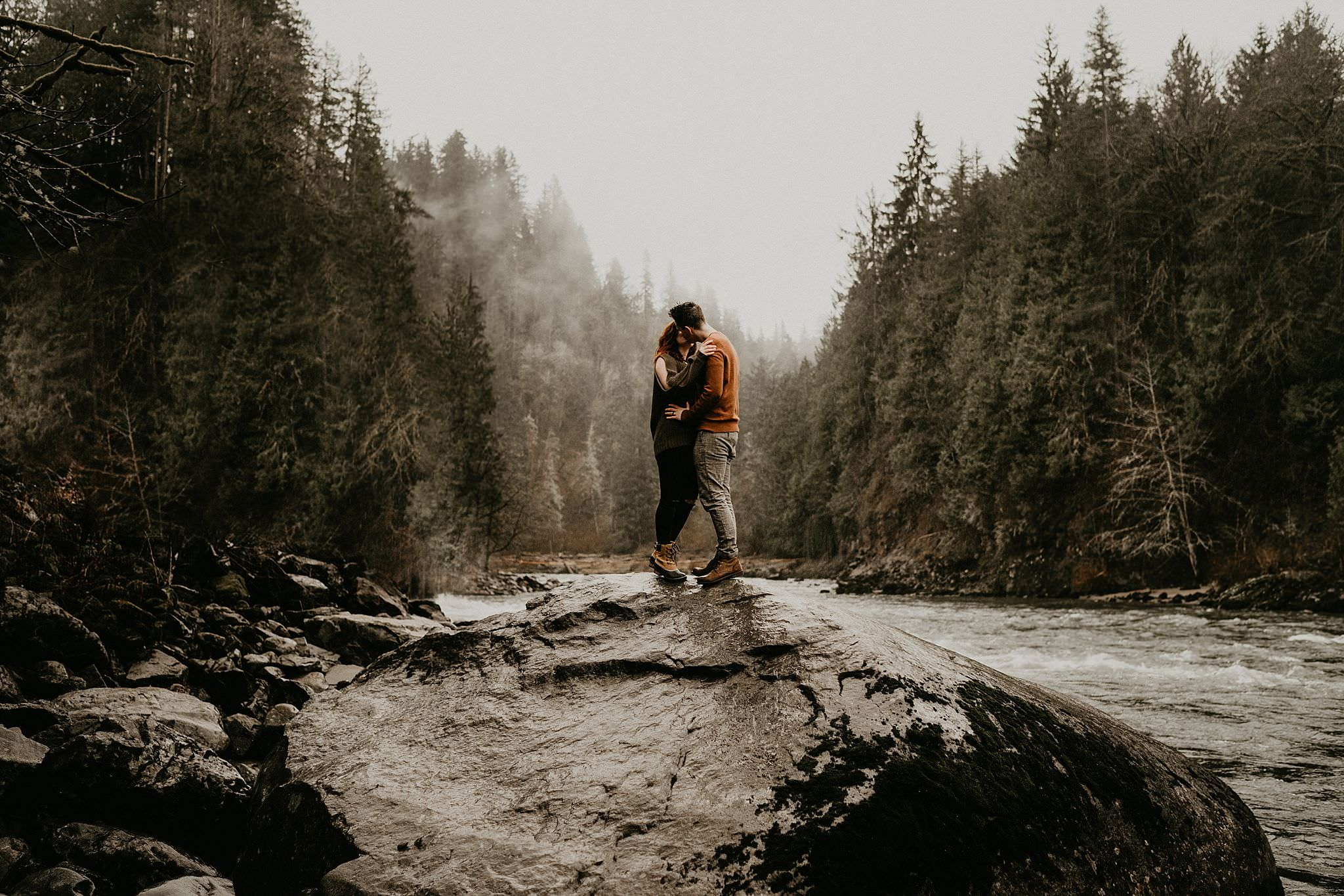 Engagement photo of couple kissing in the rain PNW weather by Snoqualmie Falls Seattle Washington