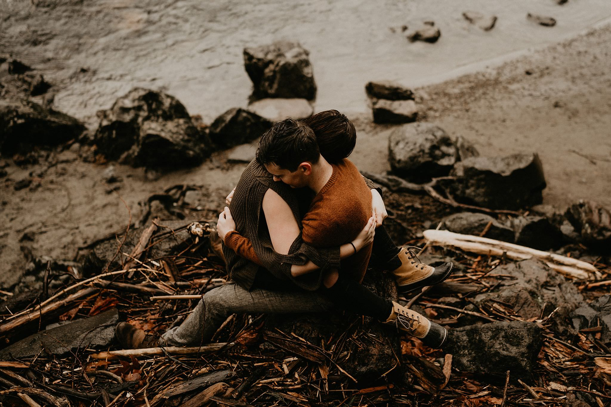 Couple holding each other in front of Snoqualmie Falls in the rain