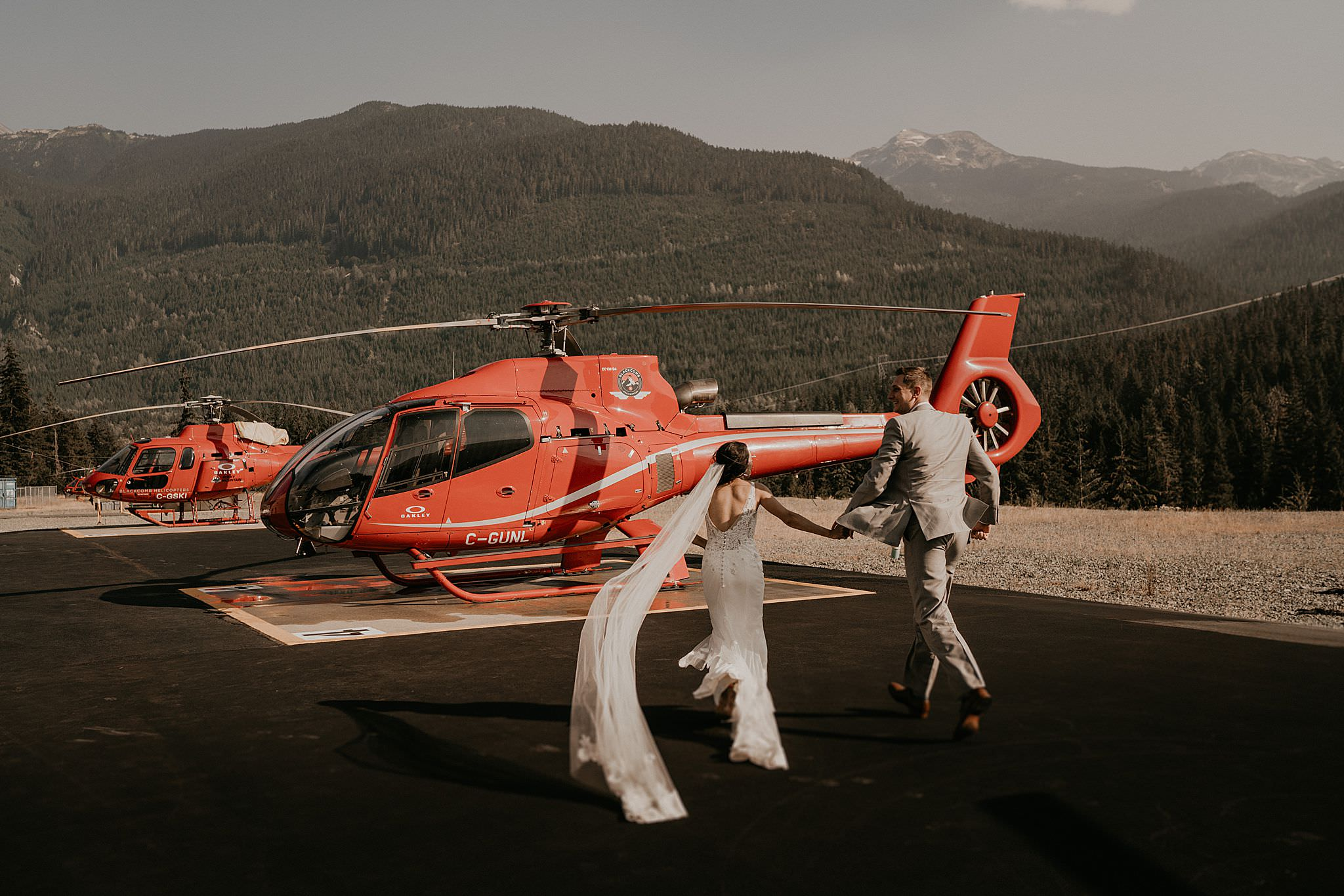 Bride and groom running to Blackcomb helicopter wedding
