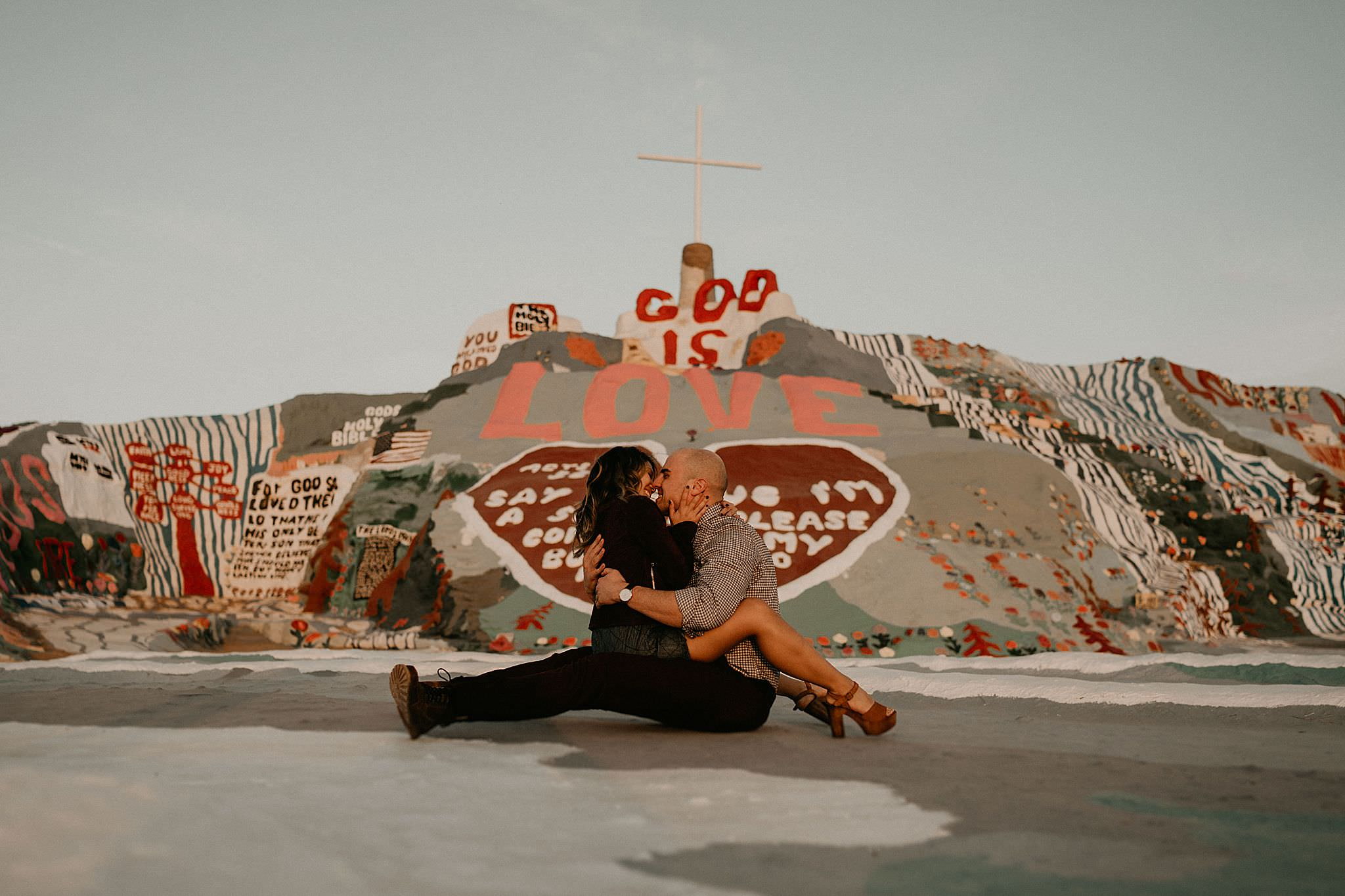 Couple kissing at salvation mountain for engagement photos