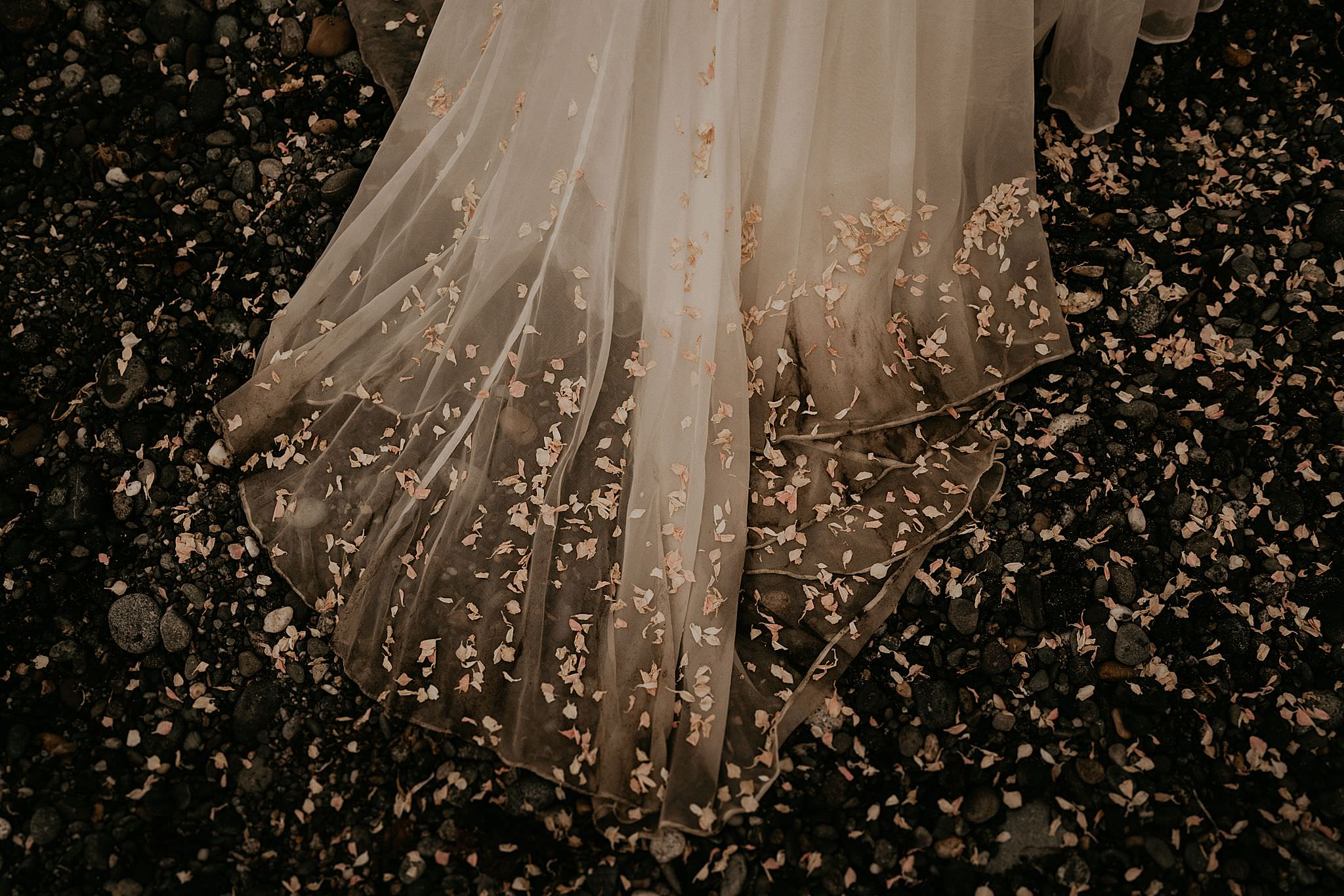 Beautiful wedding dress and dried flower petals on Whidbey Island outside of Seattle Washington