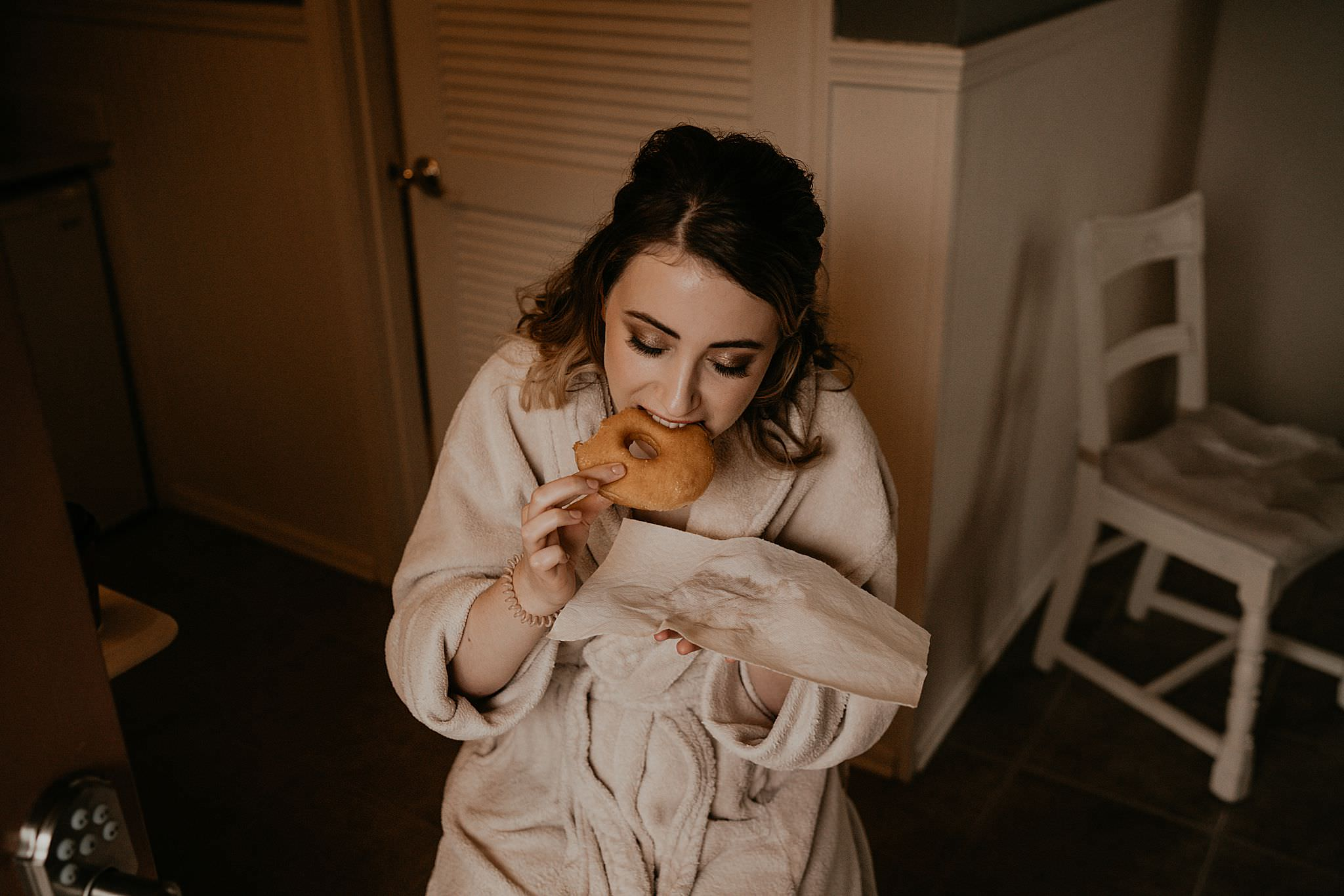 Bride eating donut while getting ready for her intimate wedding at Ebey's landing on Whidbey island
