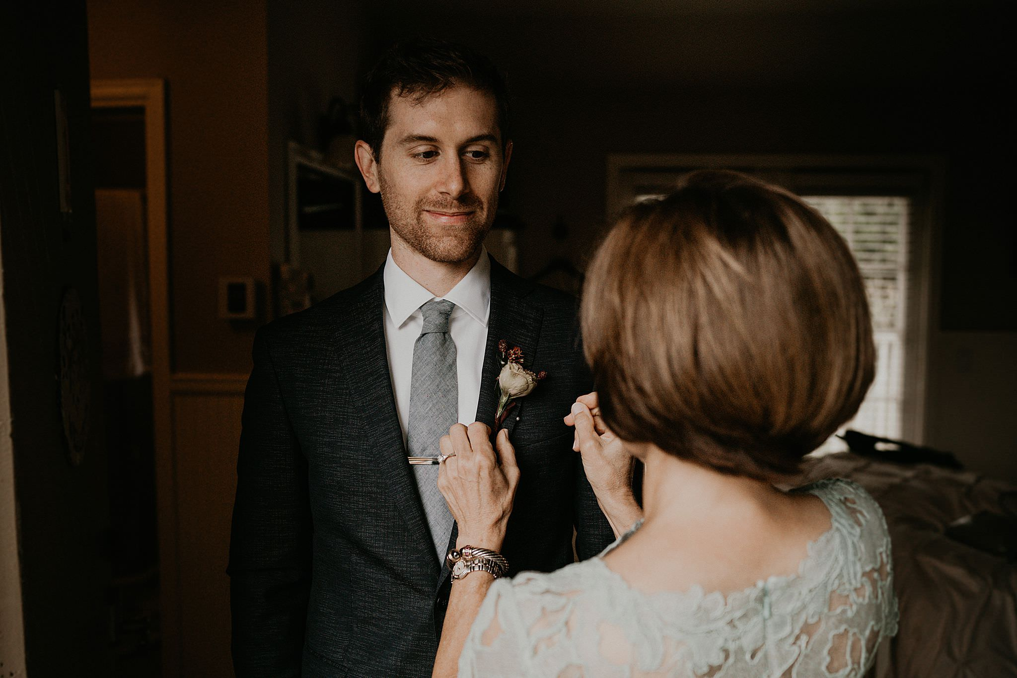 Groom getting read in his gray suit for his intimate wedding at Ebey's landing on Whidbey island