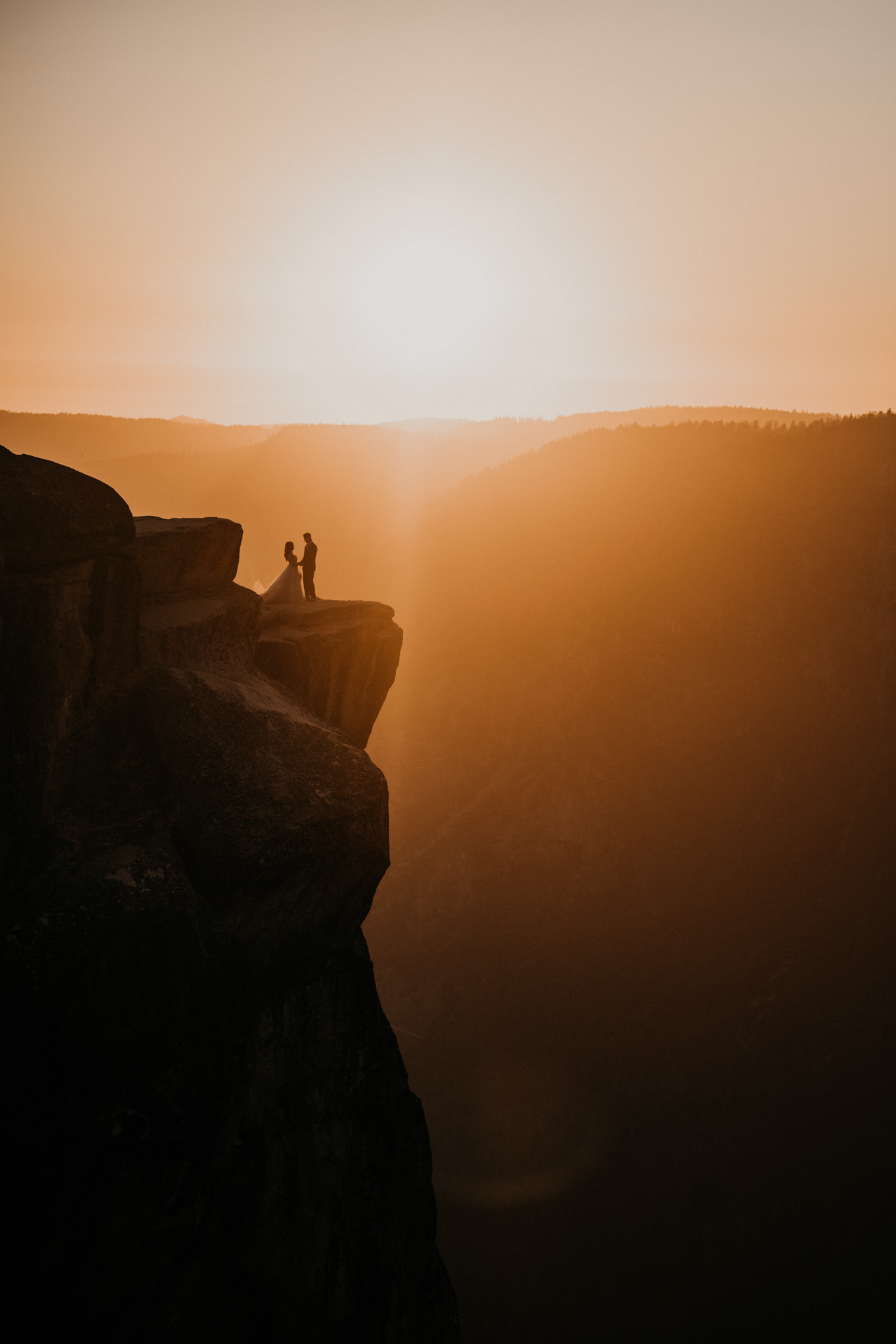 Newly wed couple beautiful light during sunset at taft point in yosemite