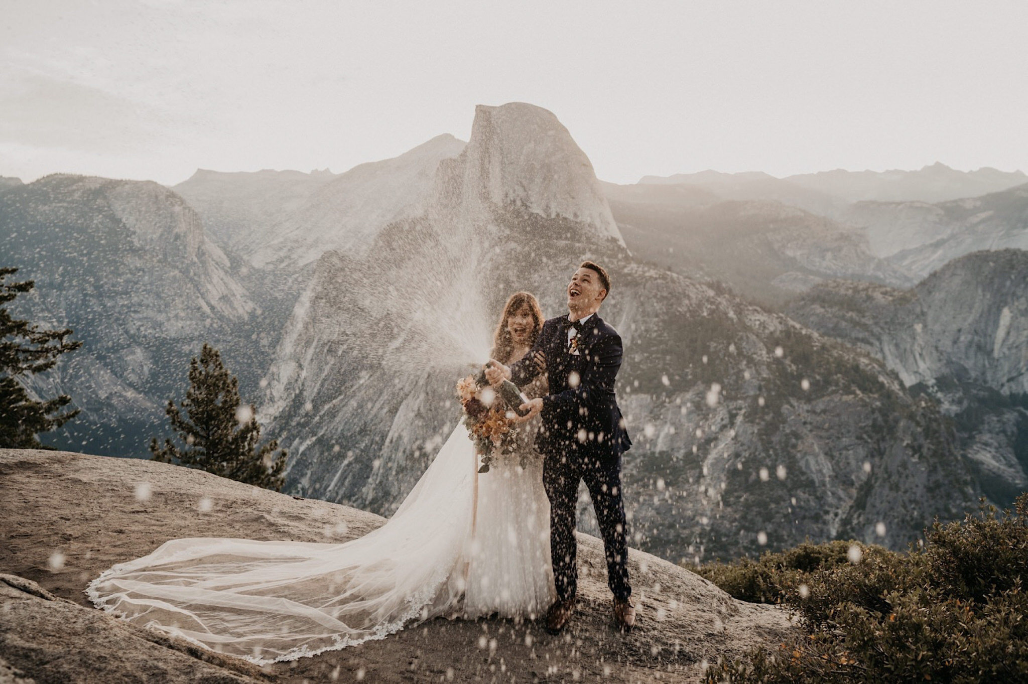 Bride and groom popped champagne to celebrate their elopement at Yosemite National Park during sunrise on Glacier Point