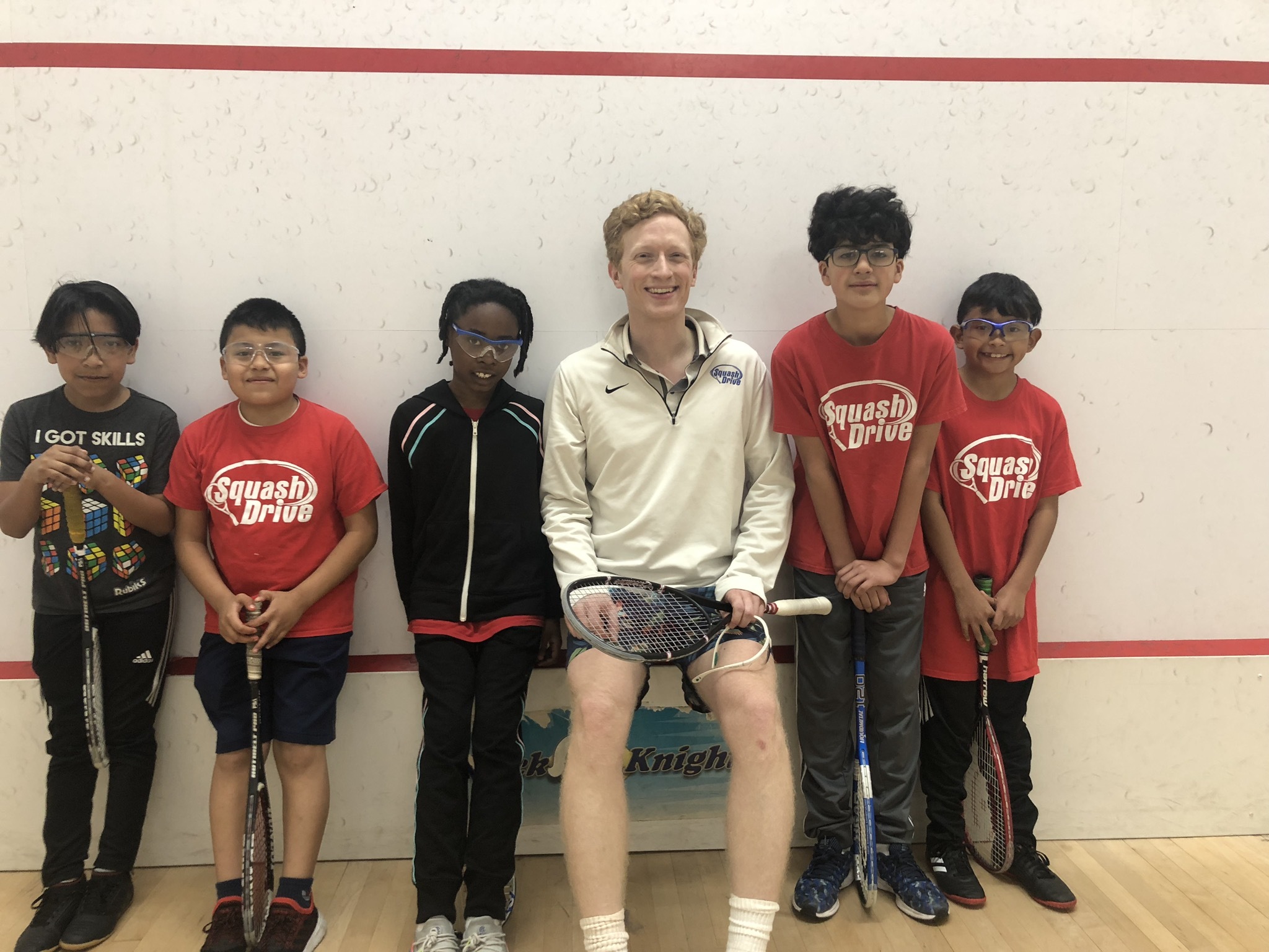 Dedicated volunteer, Peter, pictured with some of our students during squash practice!