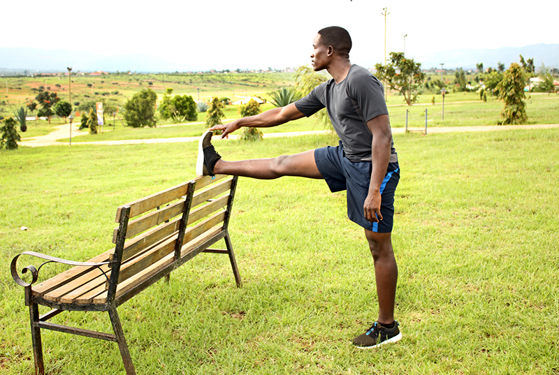 Young-Man-Stretching-Legs-on-A-Bench-in-the-Park-Before-Running.jpg