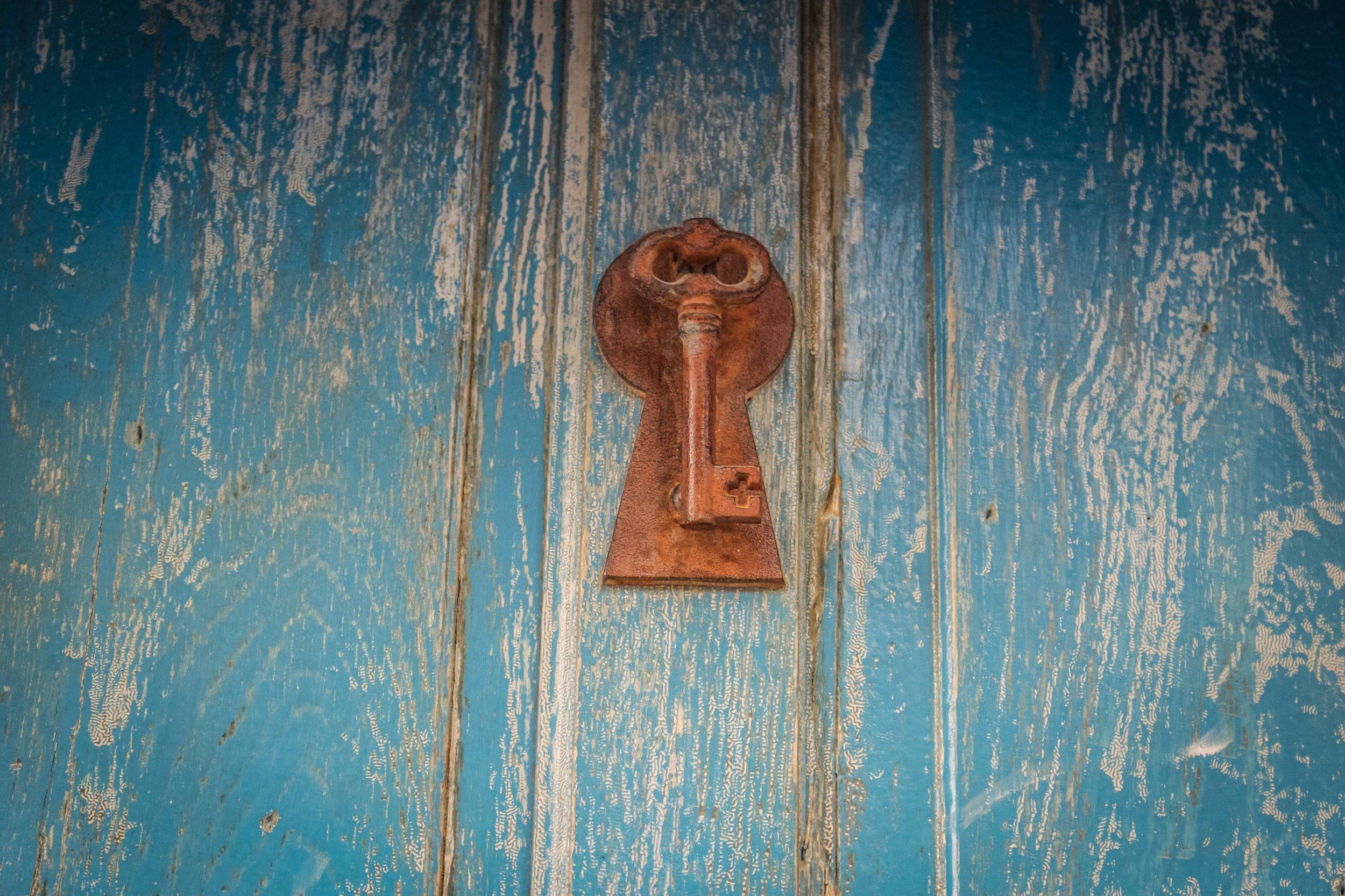 brass key on a  blue door