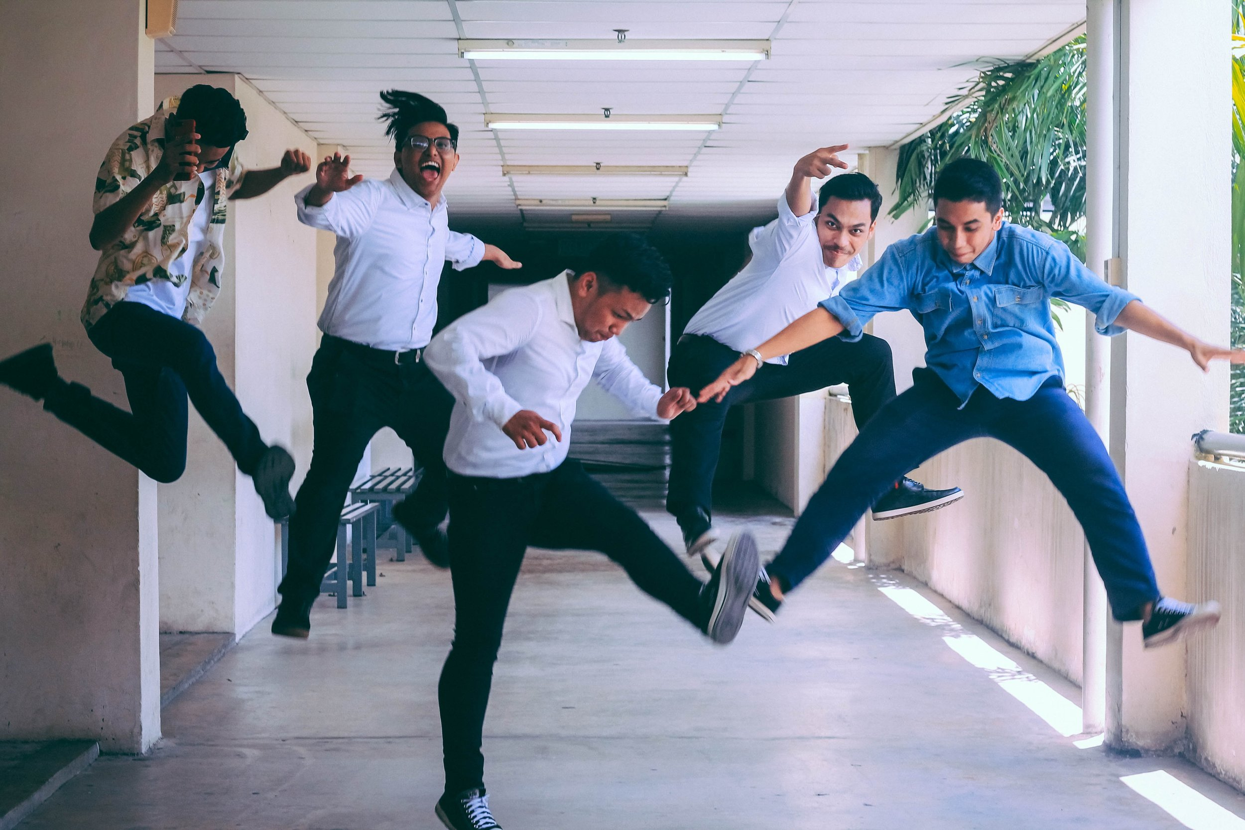 group of five people jumping in a hallway