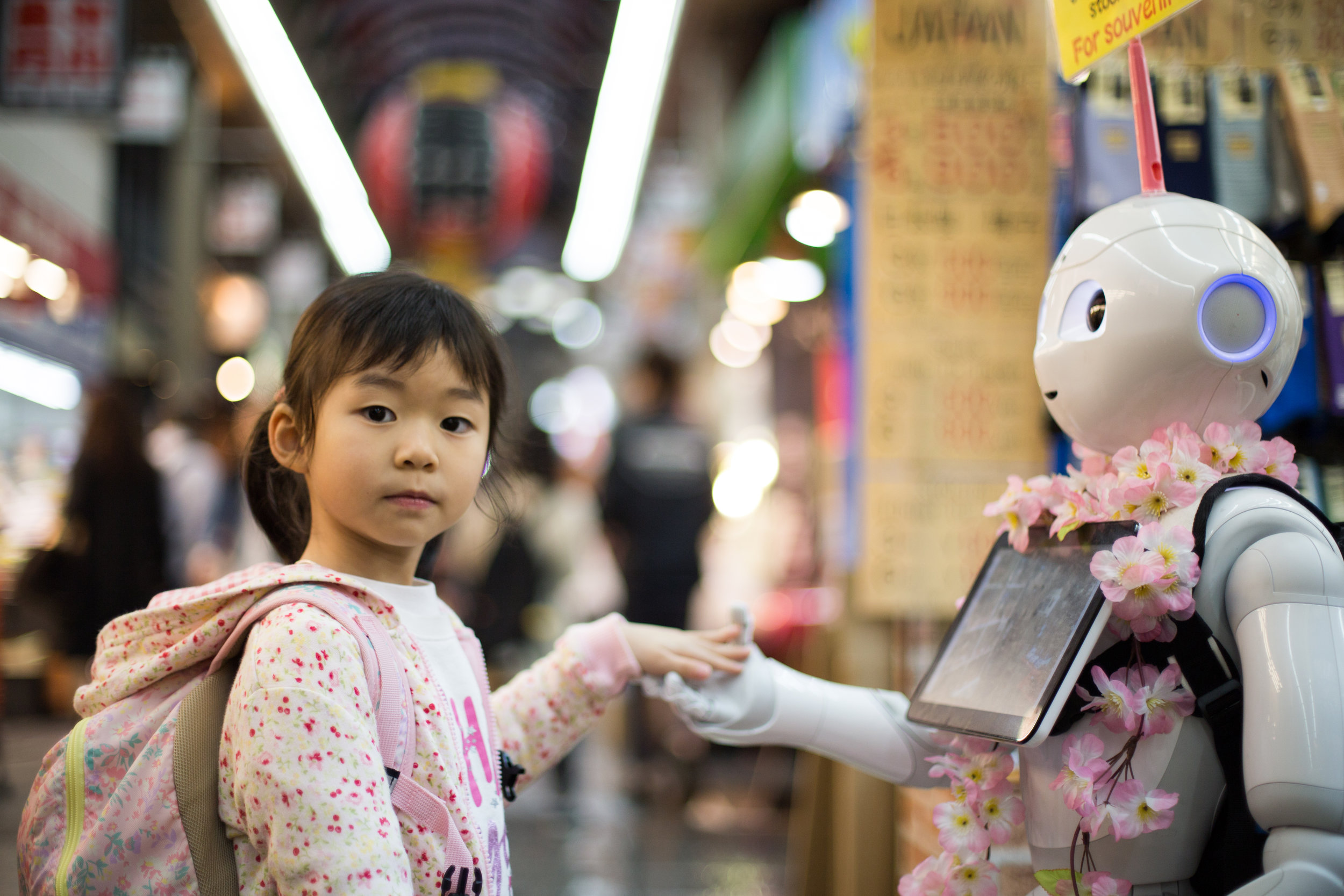 girl shaking hands with a robot