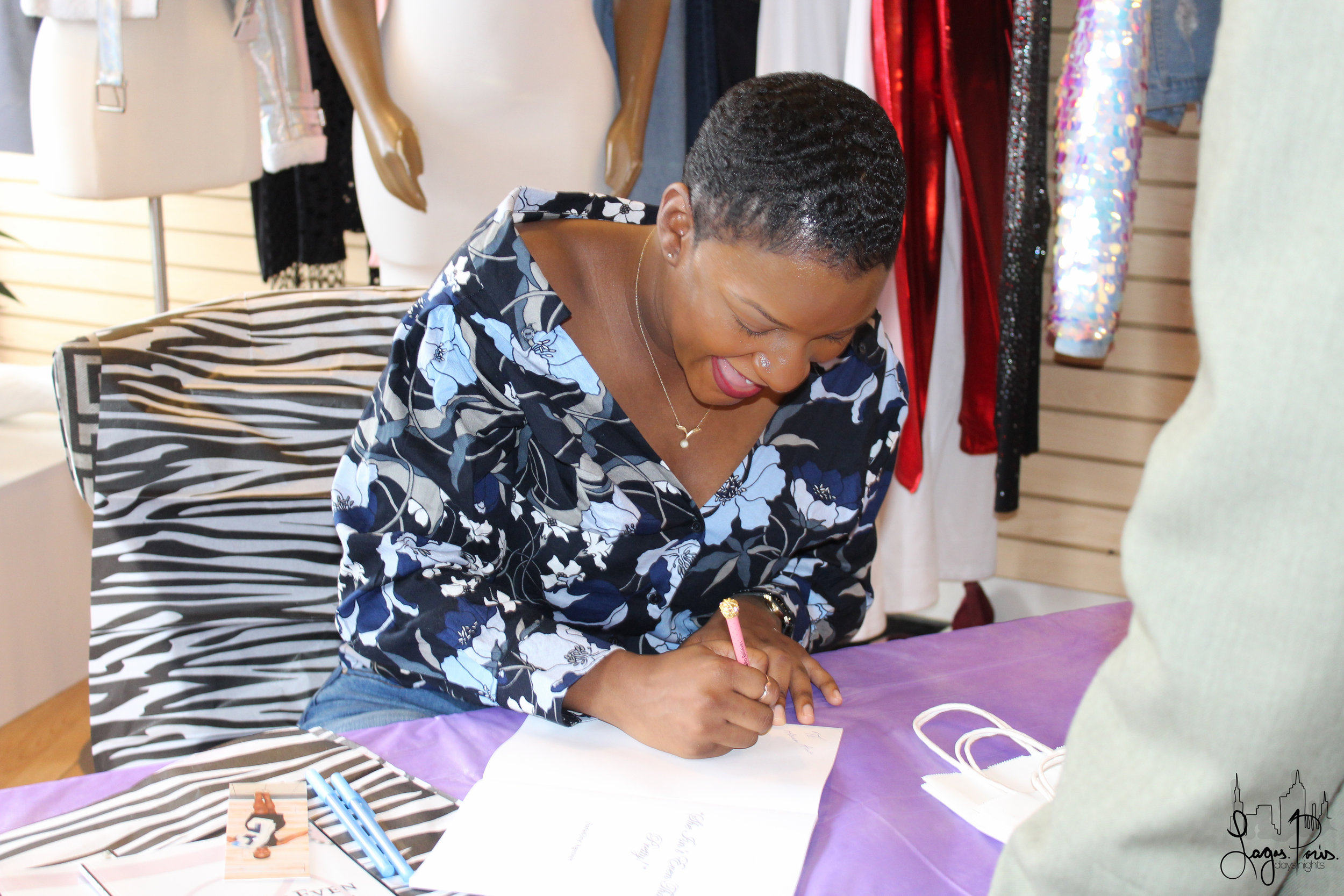 Saradjine happily signs a copy of her book for an event attendee.