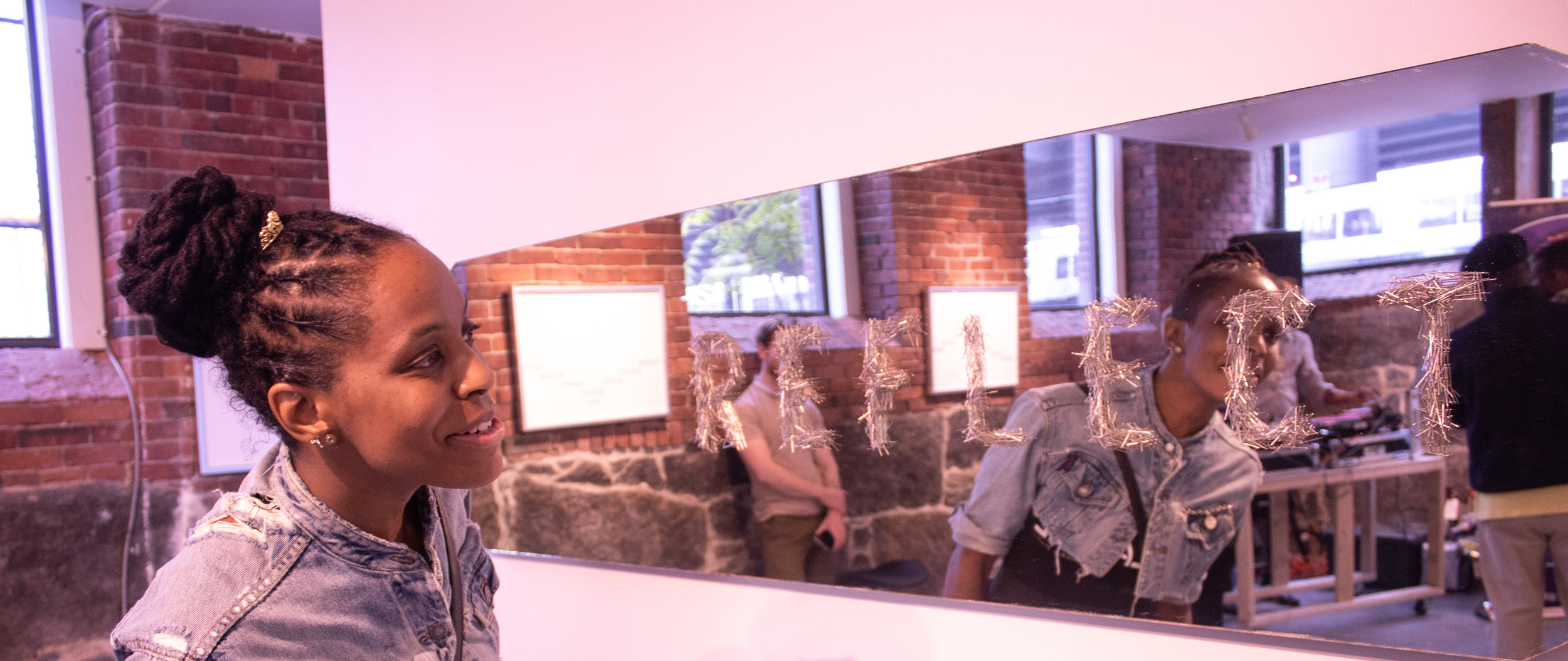 "A guest admires the art in A R E A Gallery. It reads ""reflection."""