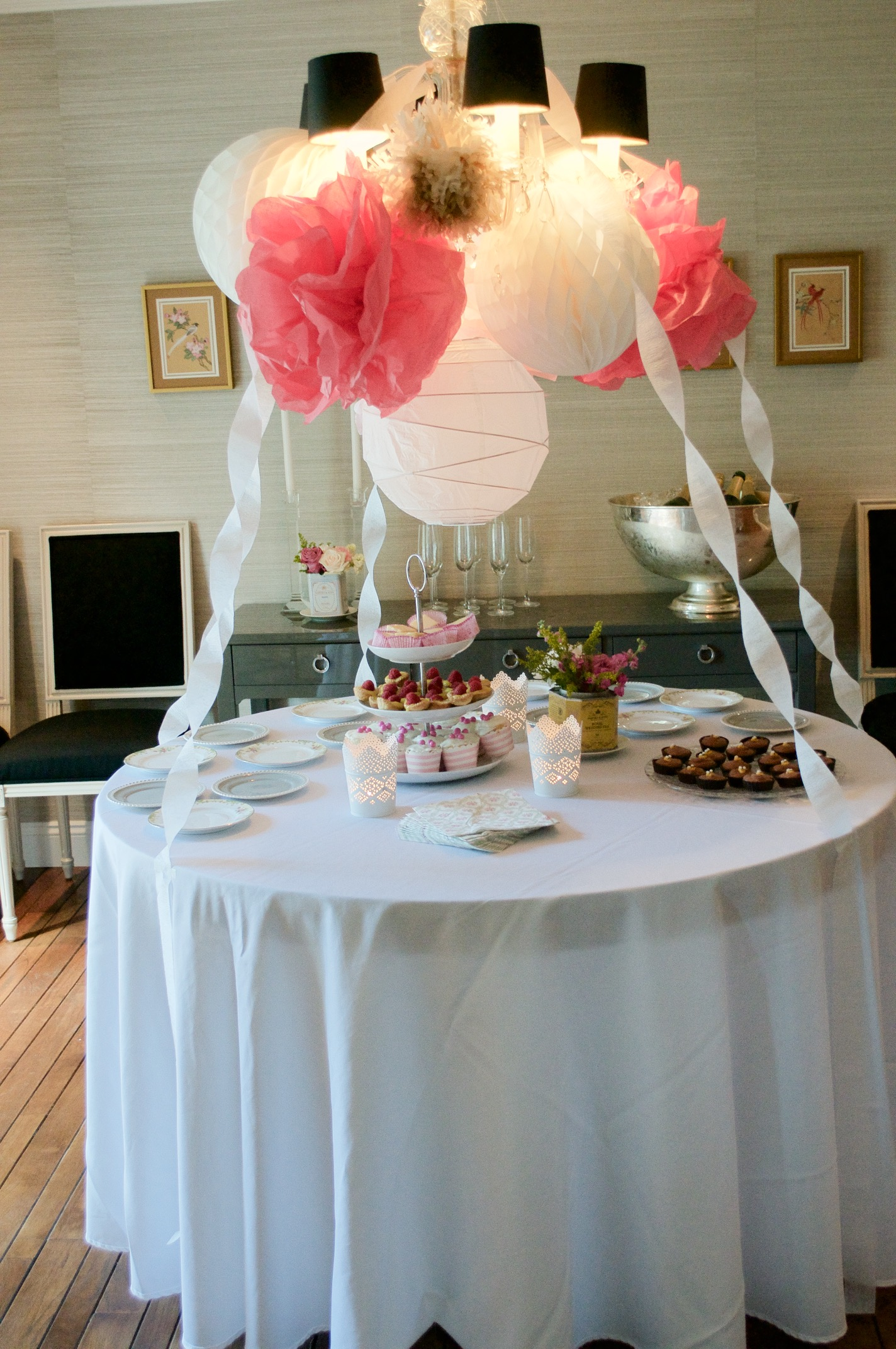 A pom pom and paper lantern display over the dessert table