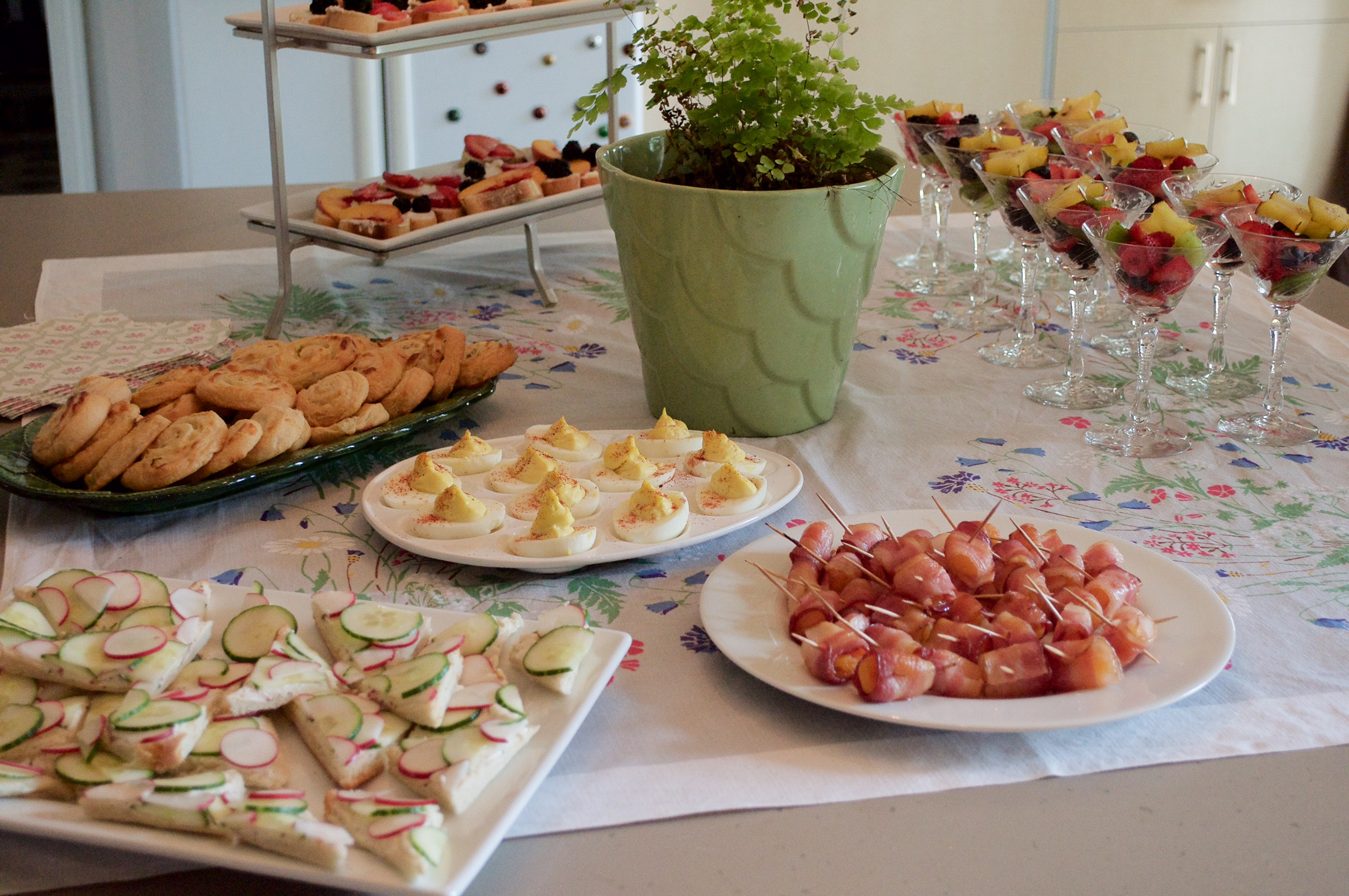 Tea sandwiches, savory baked pimento cheese pinwheels, deviled eggs, bacon-wrapped apricots, goat cheese honey and fruit crostini