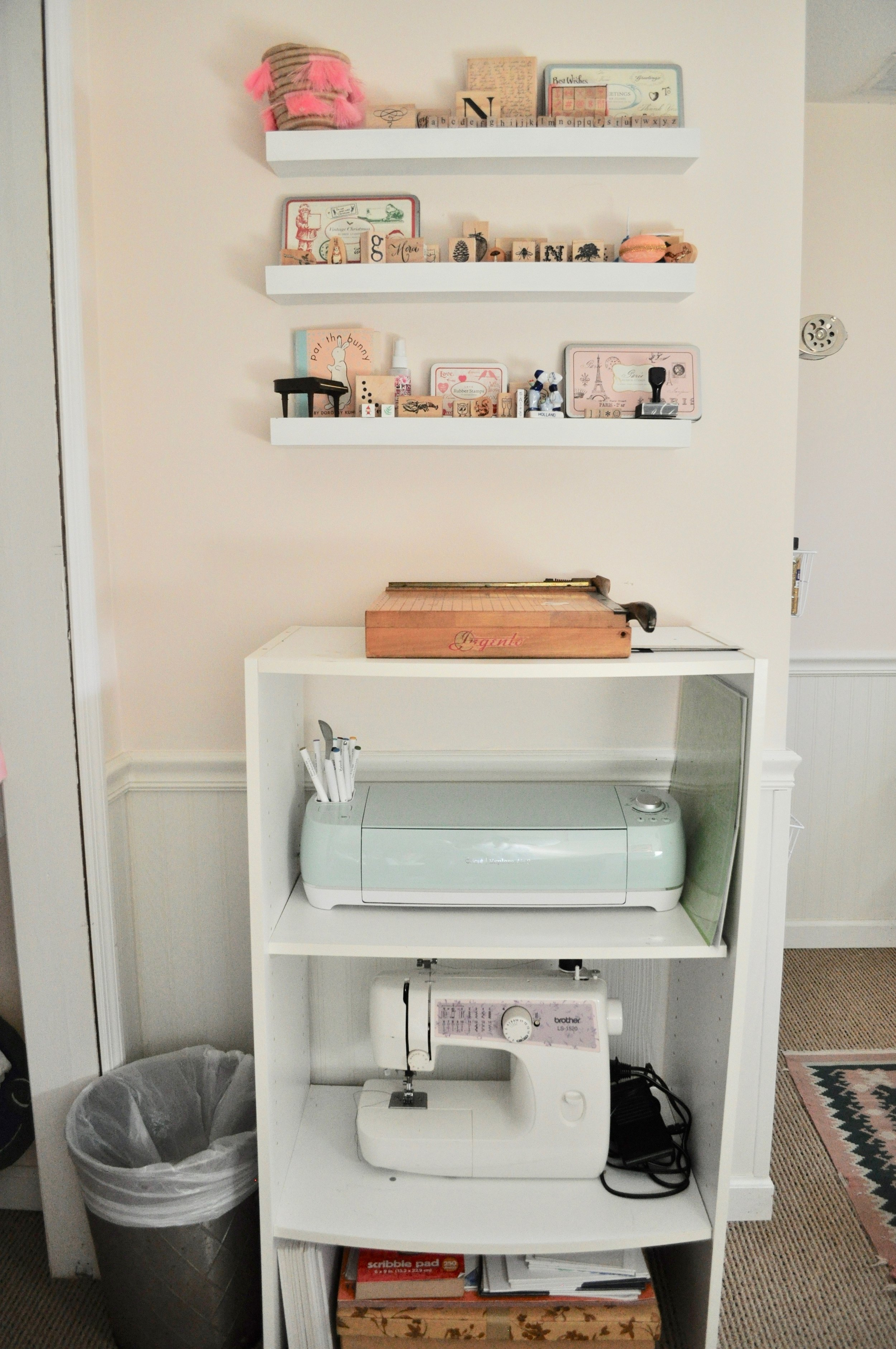 I can see all of my stamps displayed on floating shelves, and use this chopping block paper cutter at least once a week; shelves below house my Cricut and sewing machine