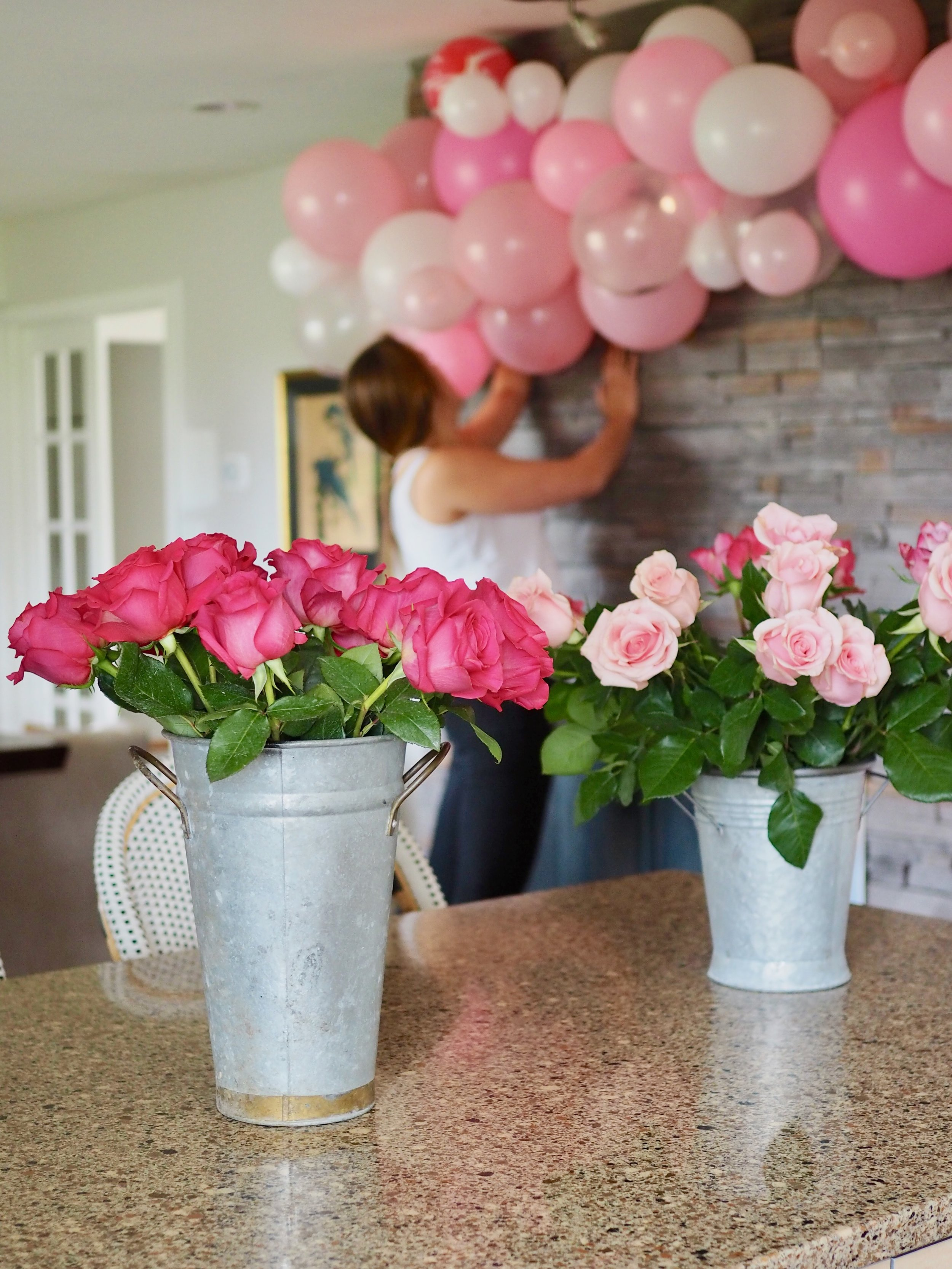 French market-style roses and Christina putting the finishing touches on a pink balloon garland