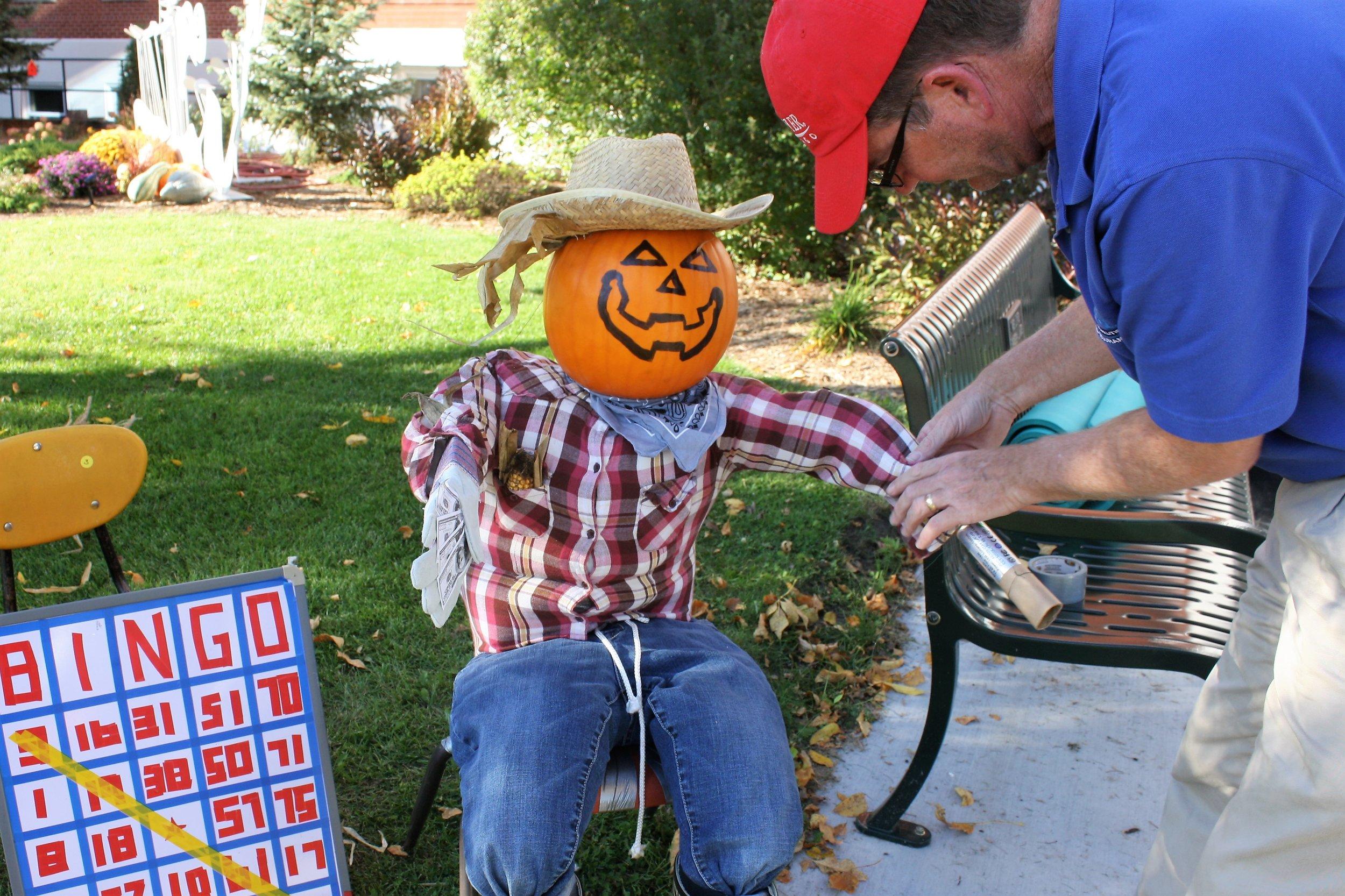 Harvest Fest Green Lake Renewal Board Member Phil Burkart prepares a Welcome Scarecrow at Harvest Fest Bingo
