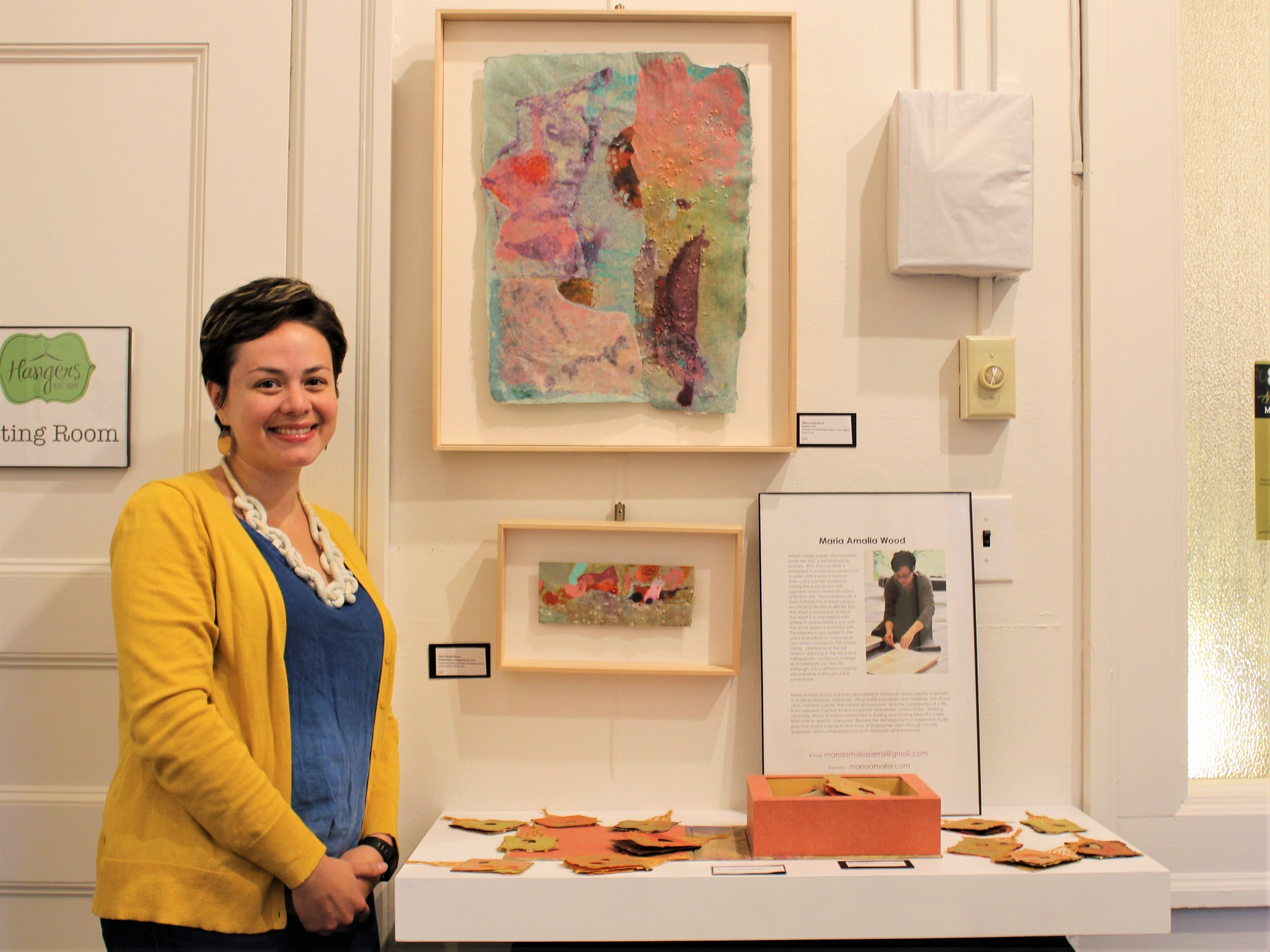 """Winner of the 2017 Midwest Paper Fest juried show, Maria Amalia Wood, poses next to her artwork. Her winning composition featured leaves made of handmade paper accompanied by a short poem: """"Dancing in the wind/ falling down slowly/ a leaf celebrates freedom."""""""