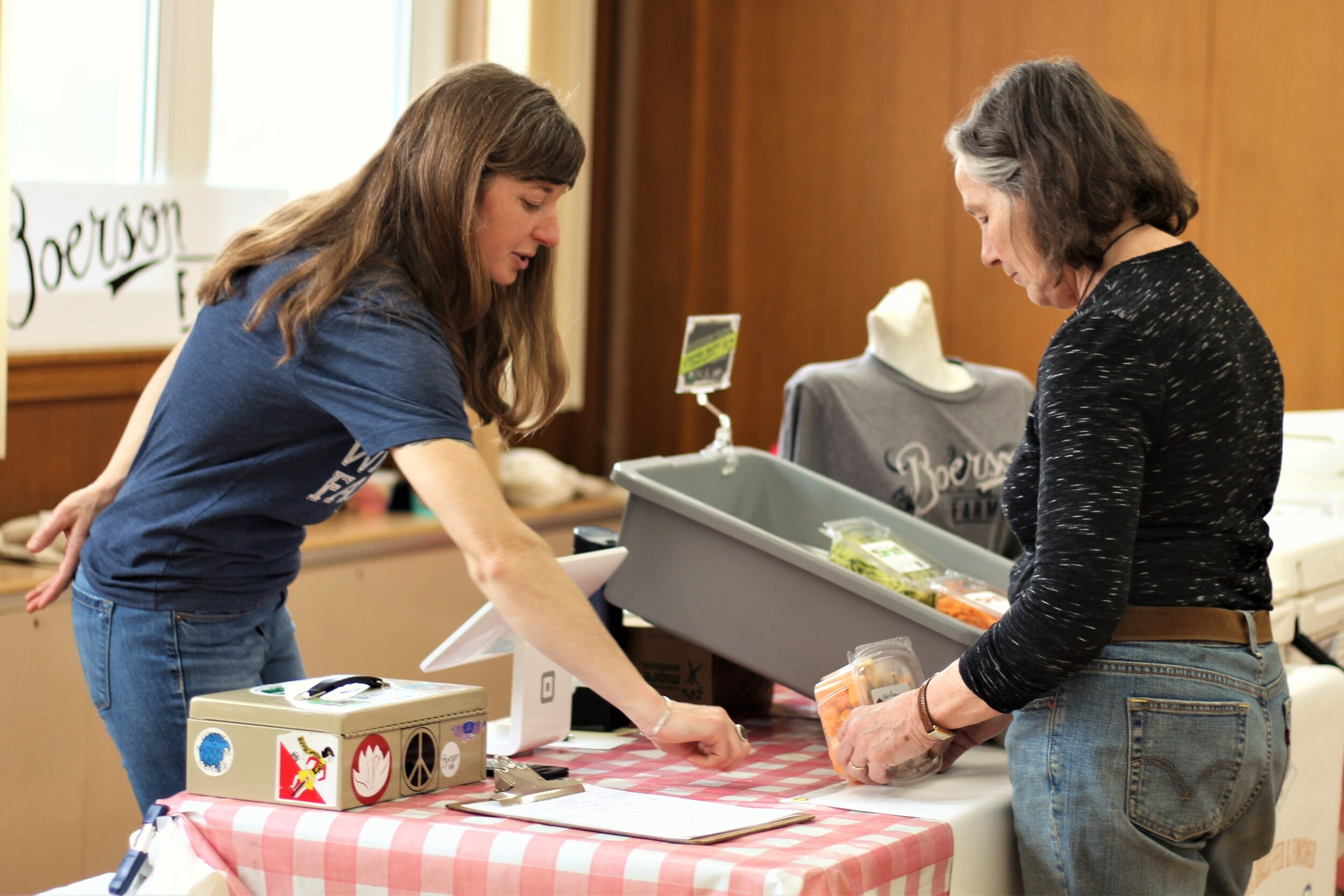 Danielle Boerson of Boerson Farm informs Sue McConnell of the benefits to buying local.