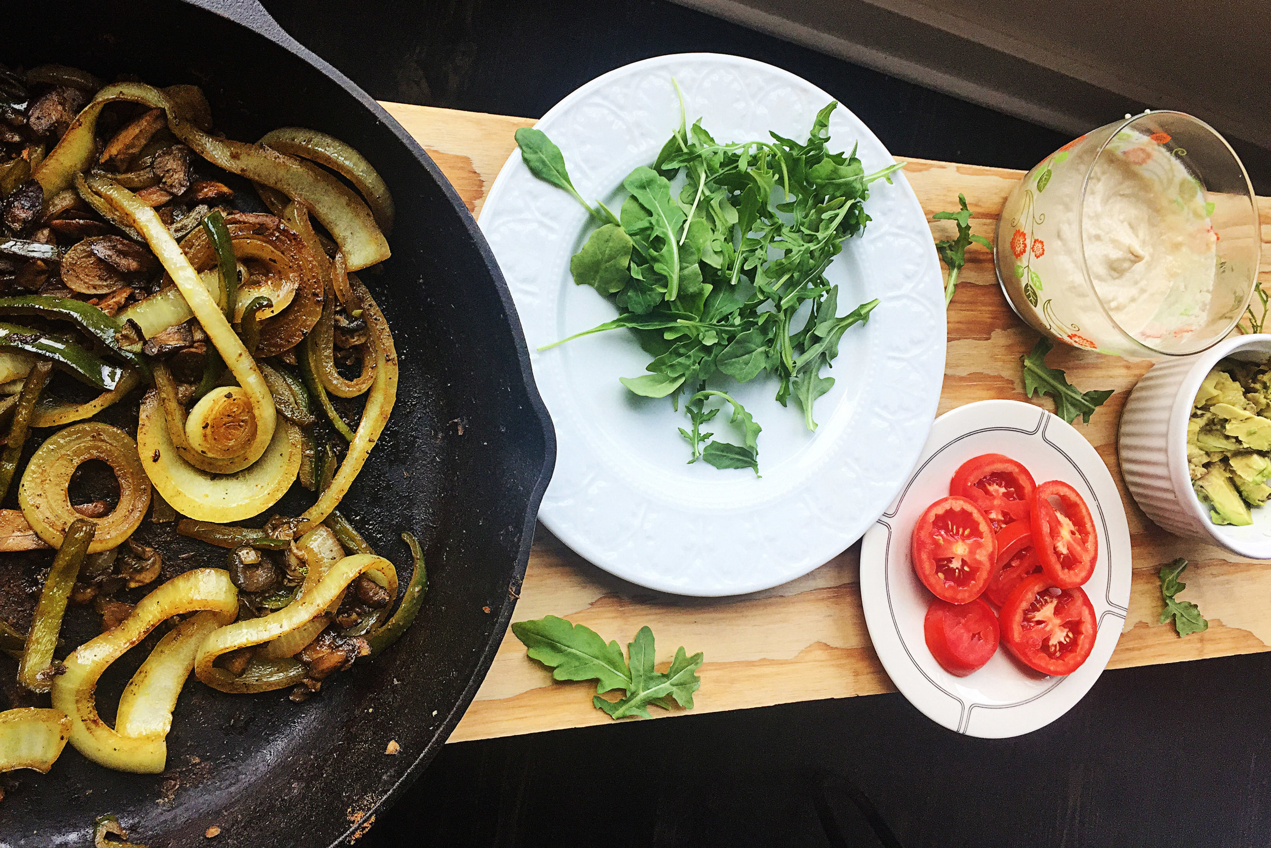 7. The final step is to prep our toppings bar. Whisk together the garlic lime tahini spread, place in a serving bowl. Chop tomatoes and avocado. Grab some arugula. I like to serve mine as a toppings bar since not everyone loves all the ingredients, so they can make their own.