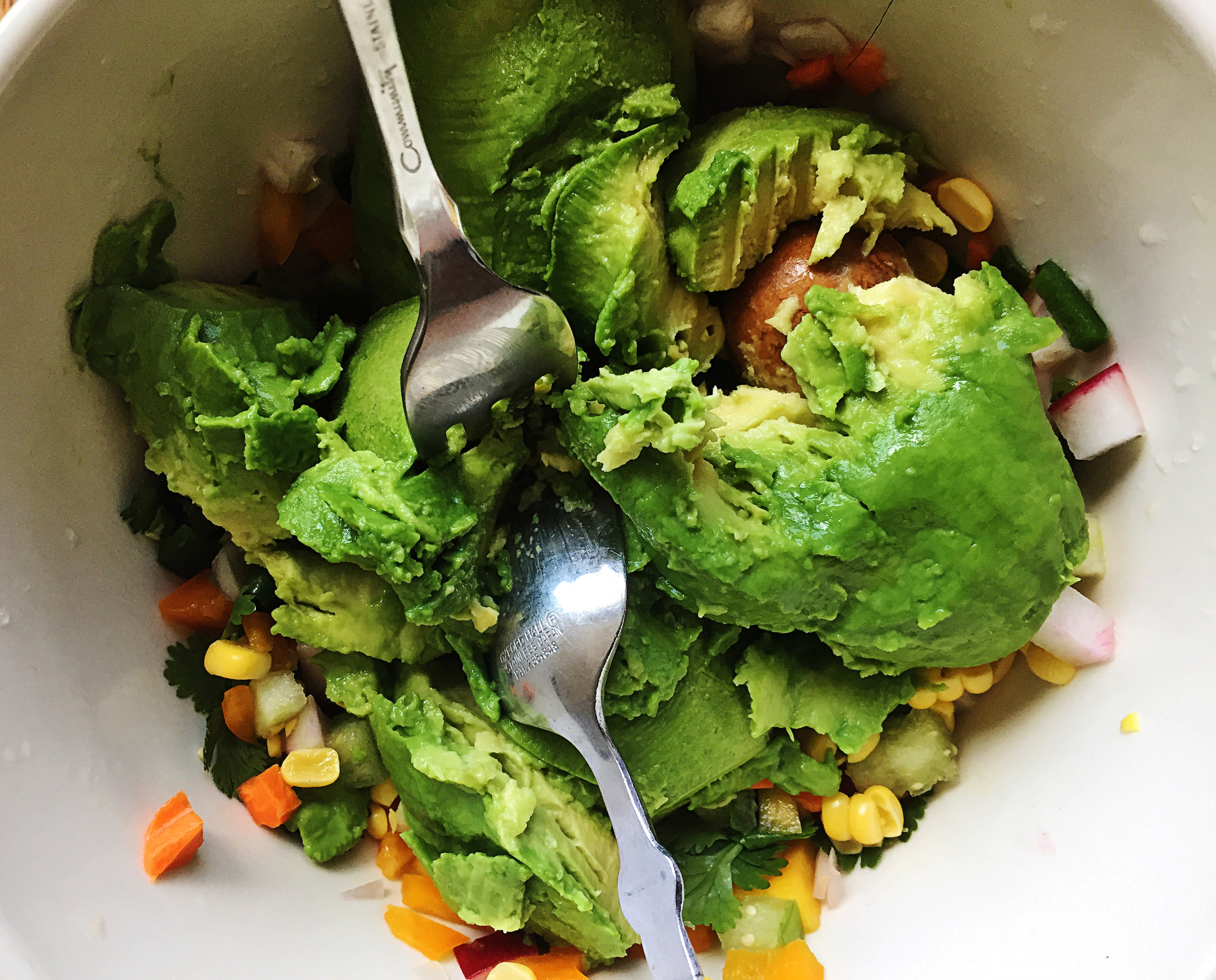 3. Next add your avocados. Cut down the middle and squeeze out all the flesh and pits into the bowl. Grab a fork + spoon. Reverse the fork + spoon direction as you see above. Press down and push out. Continue to do this to break apart the avocado.