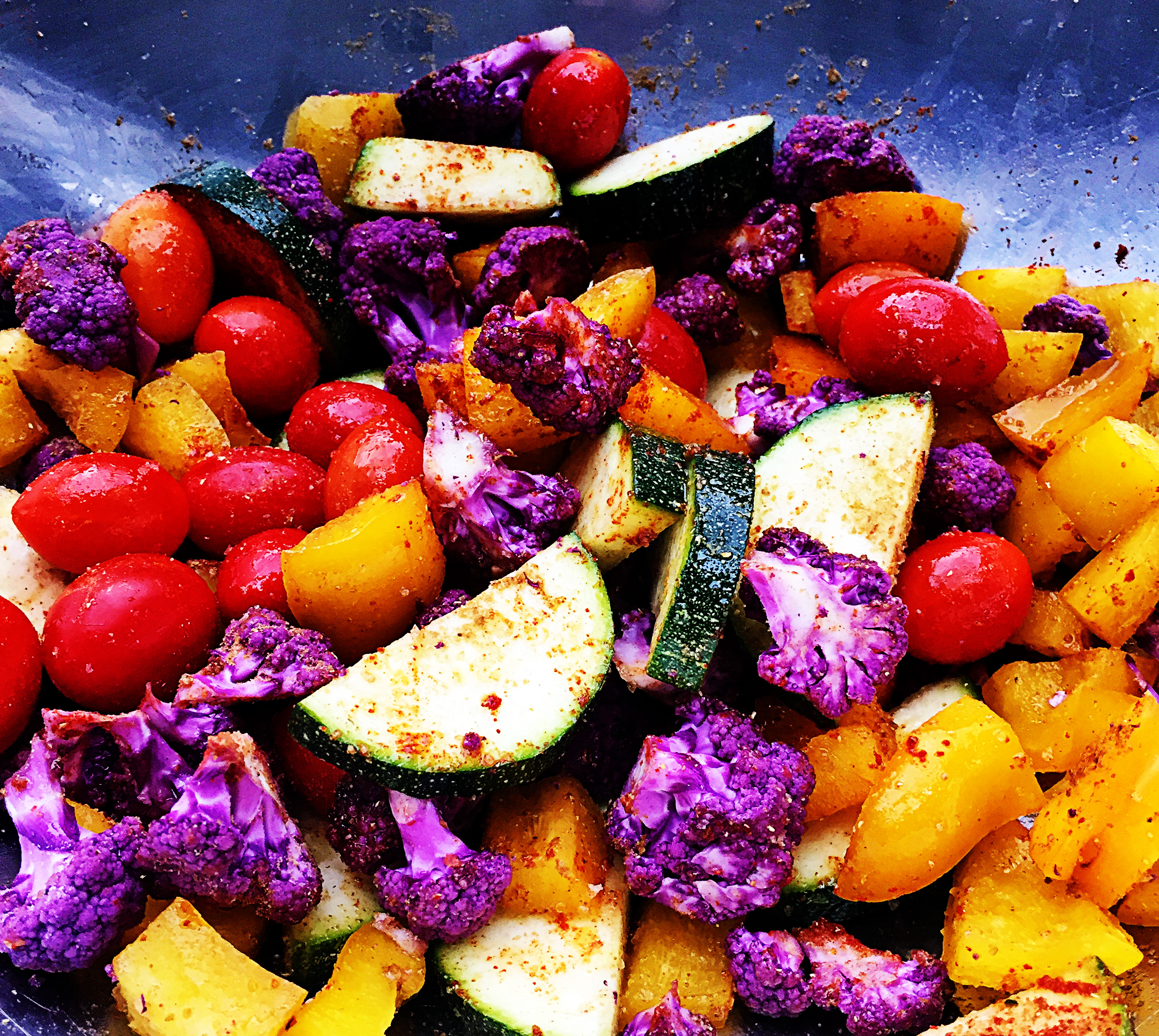 3. While your potatoes and tempeh are cooking, mix the rest of the fresh veggies with oil, coriander, sea salt, cumin, paprika, and chili powder. Toss a few times to coat all the veggies. Set aside.