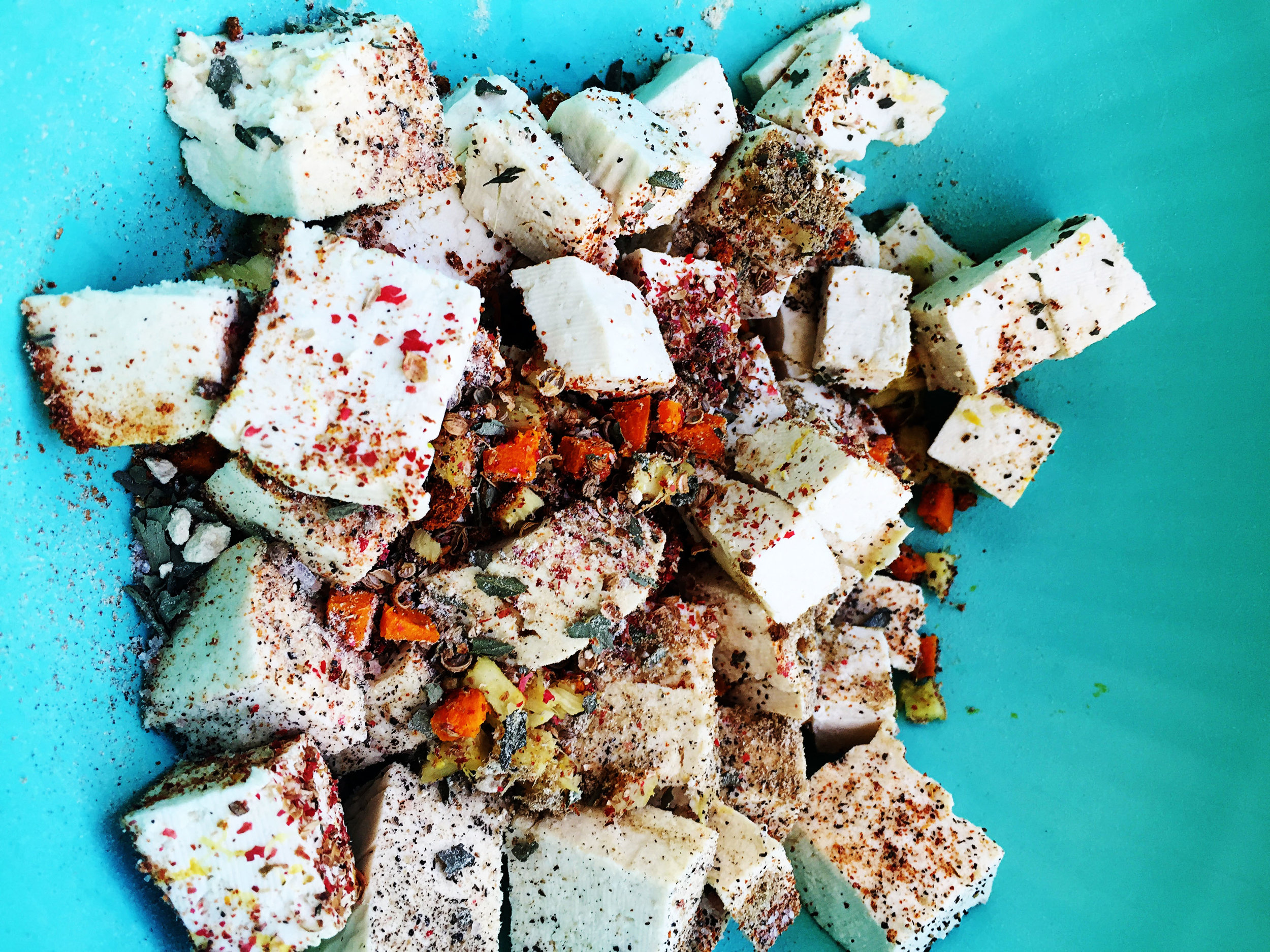 6. Put tofu, sauteed ingredients, and the rest of all spices into a mixing bowl and stir well. Place back into the pan, turn down heat a bit and saute for 6-8 minutes until tofu starts to brown and crisp on he sides.