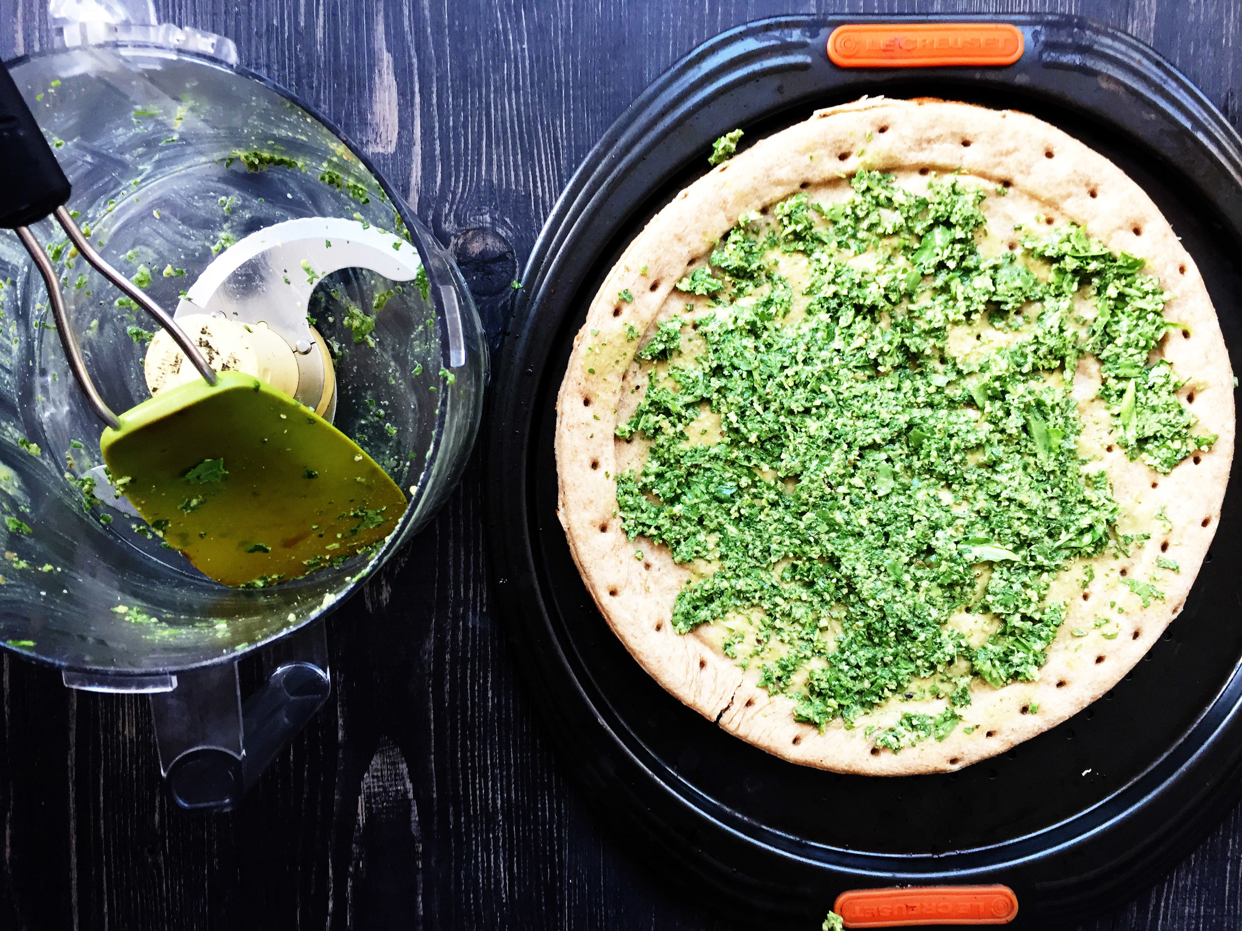 4. Take your pesto and spread it onto the pizza once it is done. We will continue to add ingredients to it. Set crust aside.
