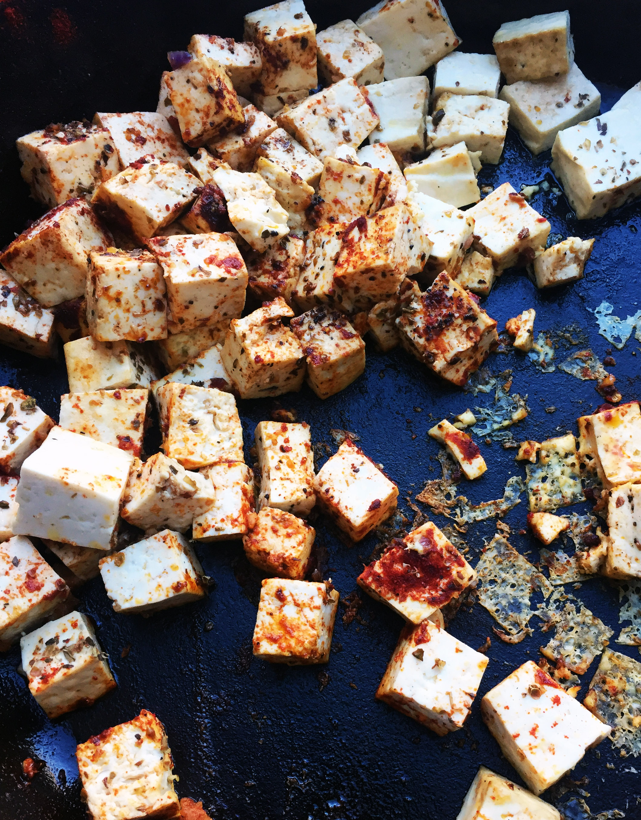 3. Place your tofu pans into your second frying pan while potatoes cook over medium low heat with oil. Cook for a couple minutes, add spices, mix well, and flip every couple mintues until a nice sear forms. Usually 8-10 minutes.