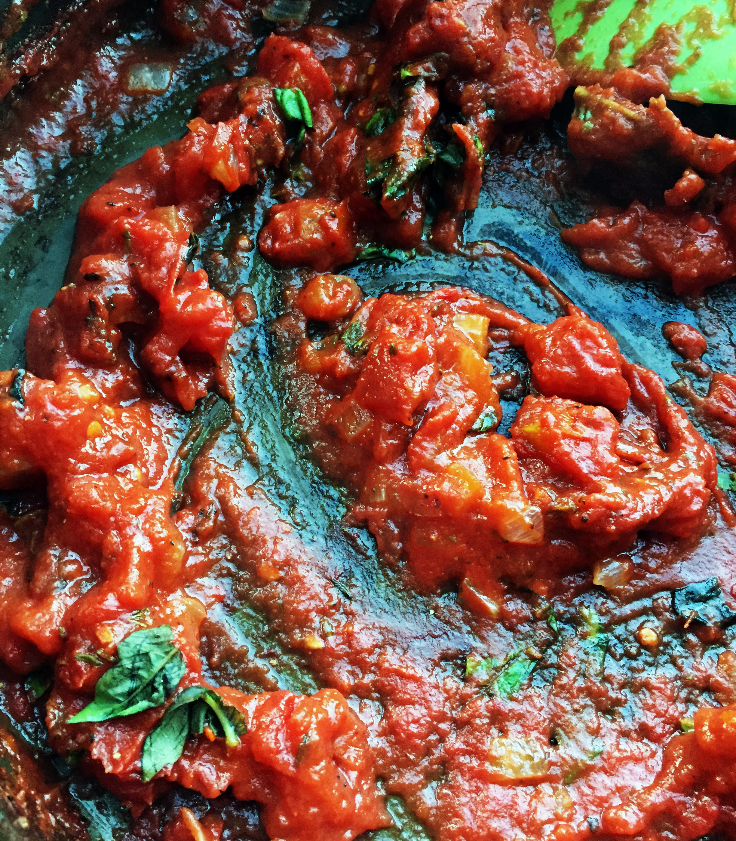 5. Add crushed tomatoes, tomato paste, spices, and basil to your pizza sauce. Reduce heat to medium-low and continue to cook for another 4-5 minutes.
