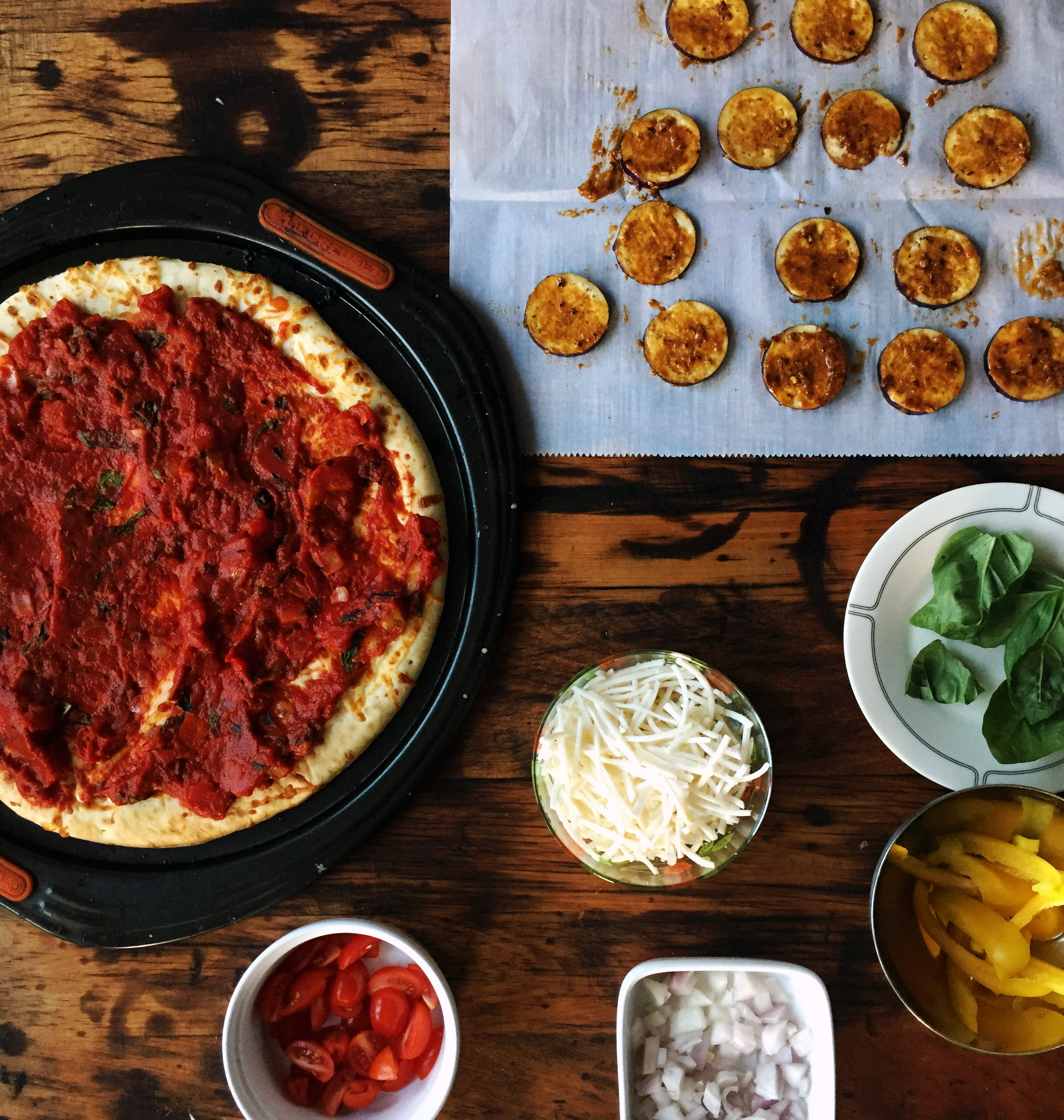 6. Set up a station to put together the pizza. Spread on the sauce to start and begin to build it in layers.