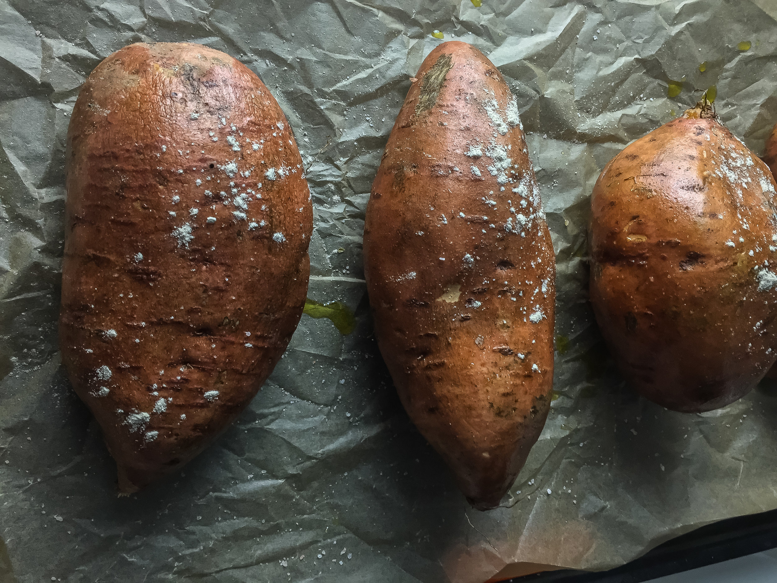 1. To start, rub olive oil and garlic salt on the potato skins. Wrap potatoes in parchment paper (I don't use aluminum foil) and bake for 45-50 minutes until a fork can pierce the potato easily and slide through with just a bit of resistance.
