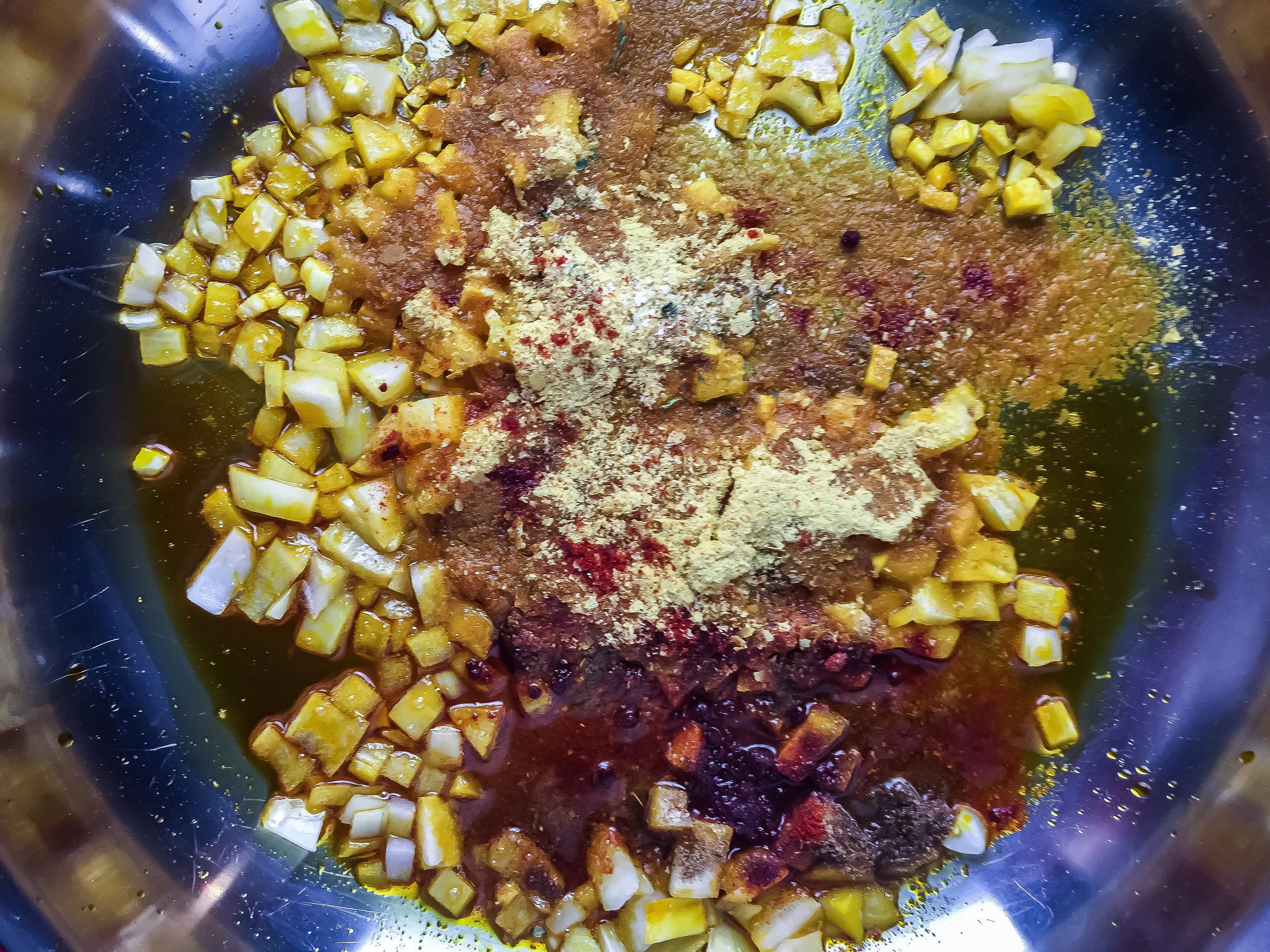 1. Start with the queso. Place palm oil in medium/large frying pan. Warm for 60 seconds over medium heat. Cook up onions and garlic for 4-5 minutes. Add in spices. Mix well. Cook another two minutes.