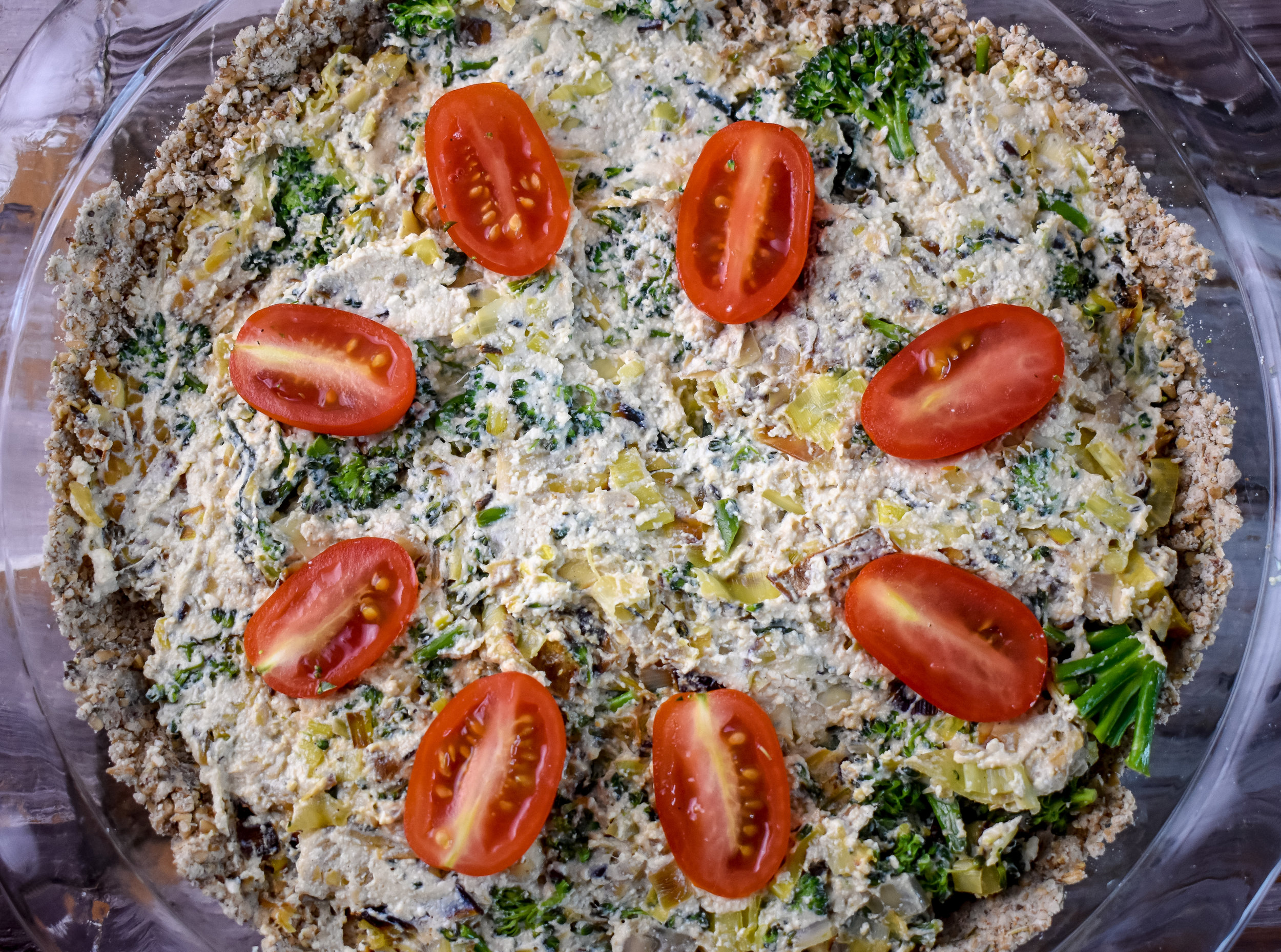 10. Spread the tofu mixture across the crust that has been baked and I like to place a few tomato halves on top of the quiche for some added flavor.