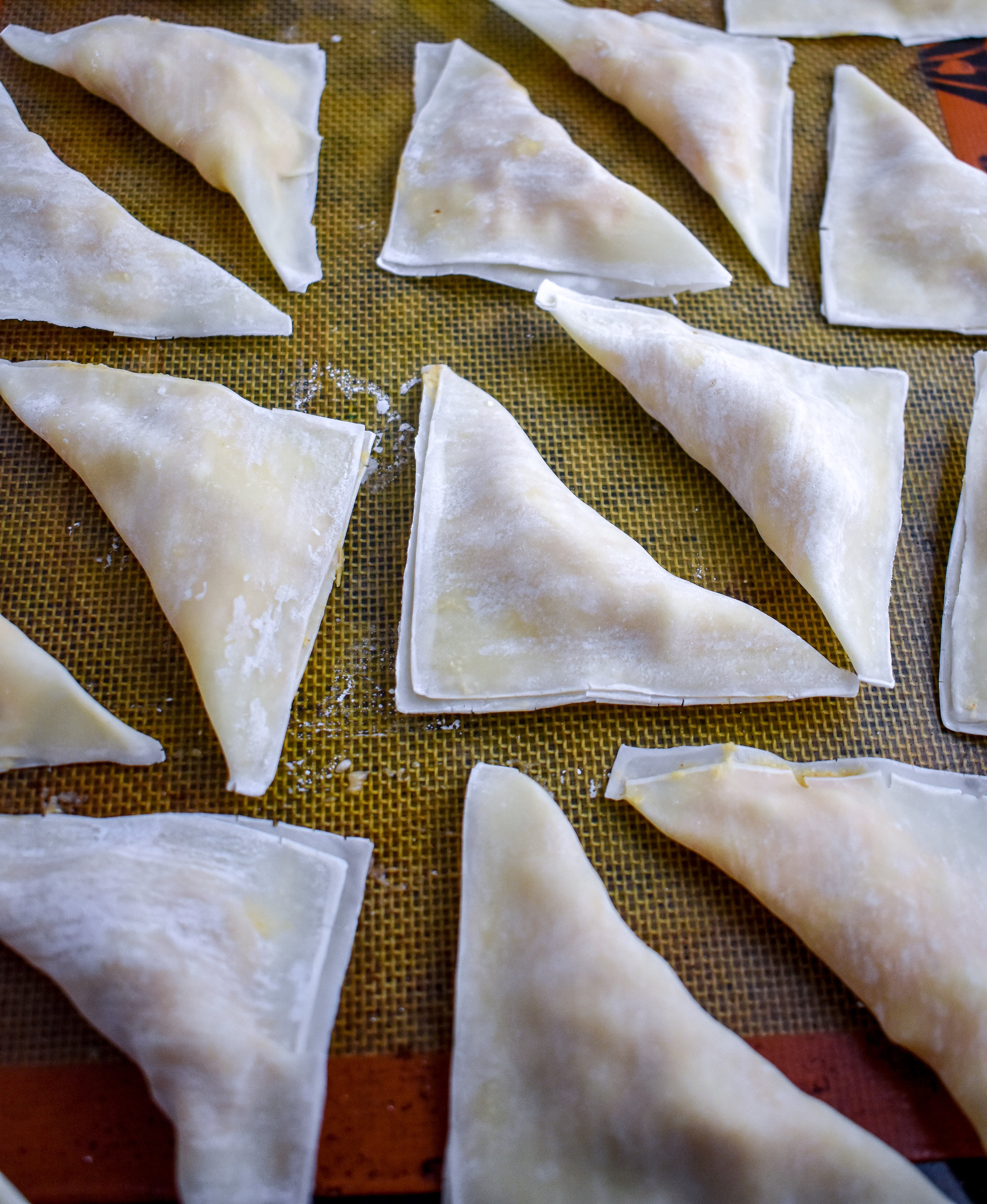 8. Line up your folded wontons on a silpat or parchment lined baking sheet and put into the oven for 15 minutes. Flip and bake another 10 minutes until the corners are golden brown and the skin has crisped.