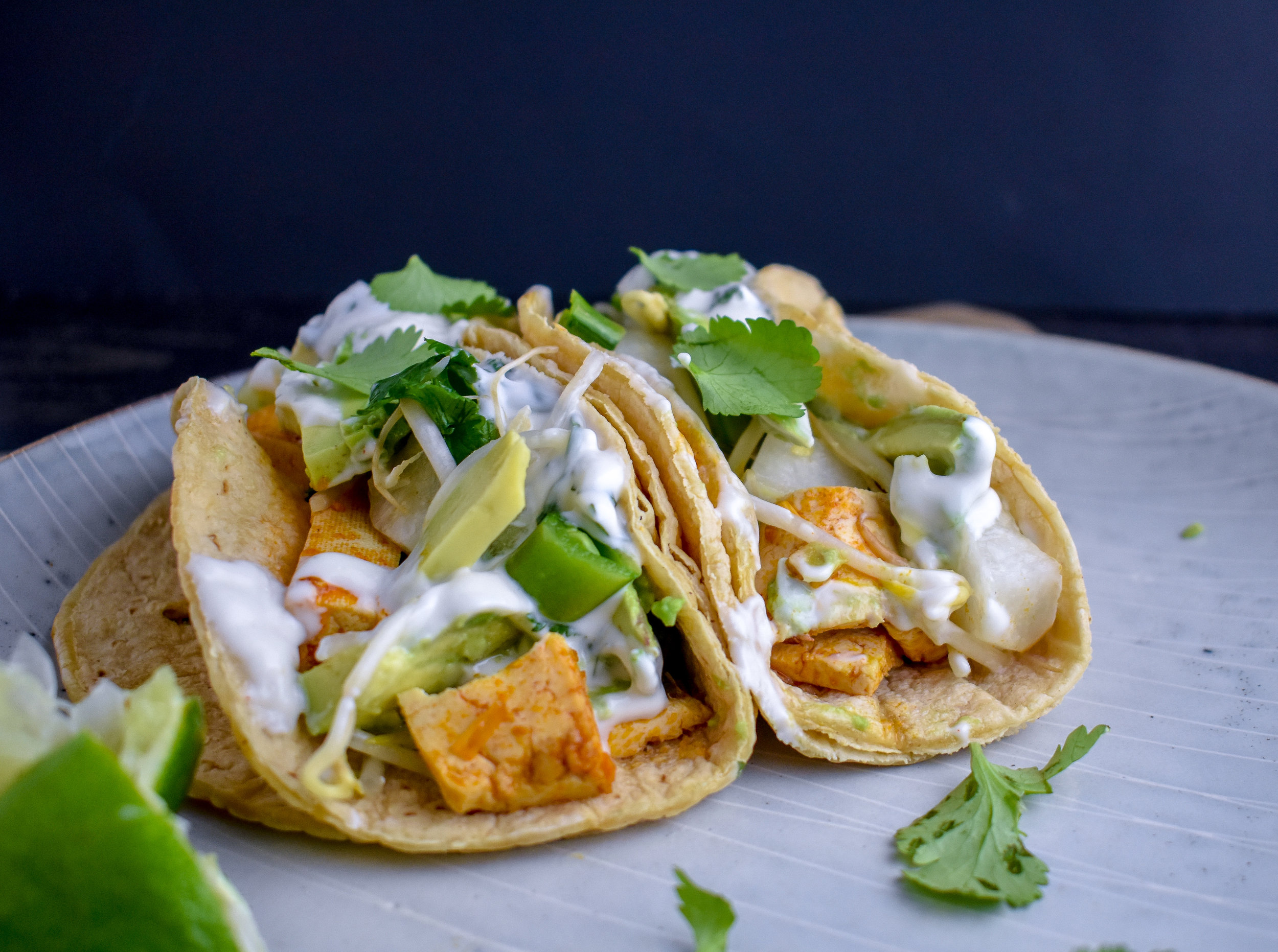 6. To form your tacos. Layer on some tofu strips, slaw, avocado slices, and the aioli. Top with a few pieces of fresh cilantro and a squeeze of lime juice to take it to the next level.