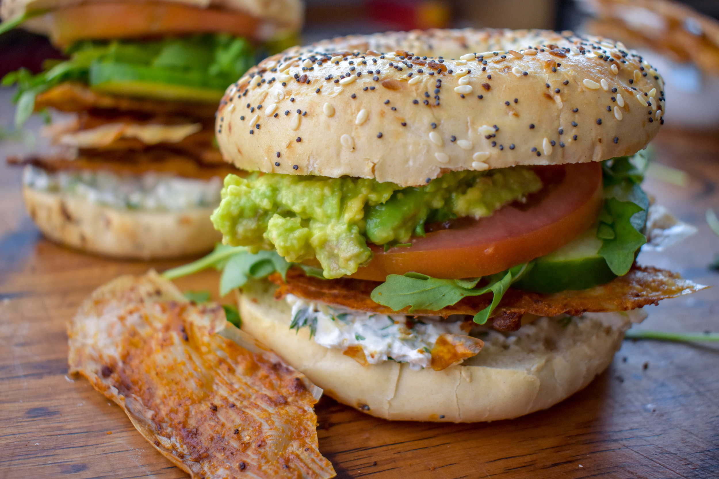 9. To construct, spread cream cheese on the bottom of the bagel. Stack on 4-5 bacon pieces. Add veggies + avocado smash. Spread a bit more cream cheese on top of the bagel. Smash it together. Eat. Enjoy!