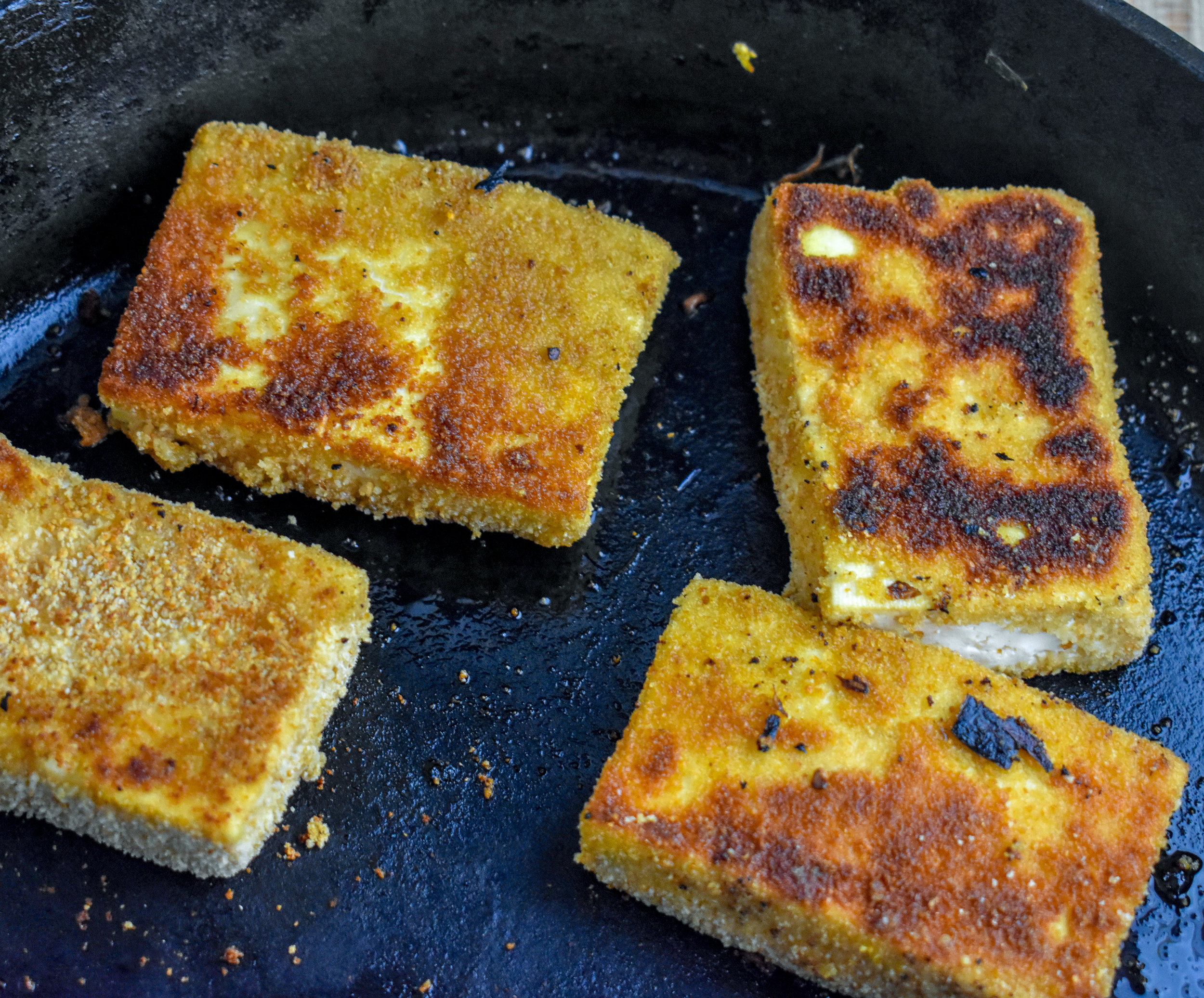 6. Once all four tofu cutlets are breaded, add to castiron pan, turn heat to medium low. cook for 3 minutes until golden brown on each side.