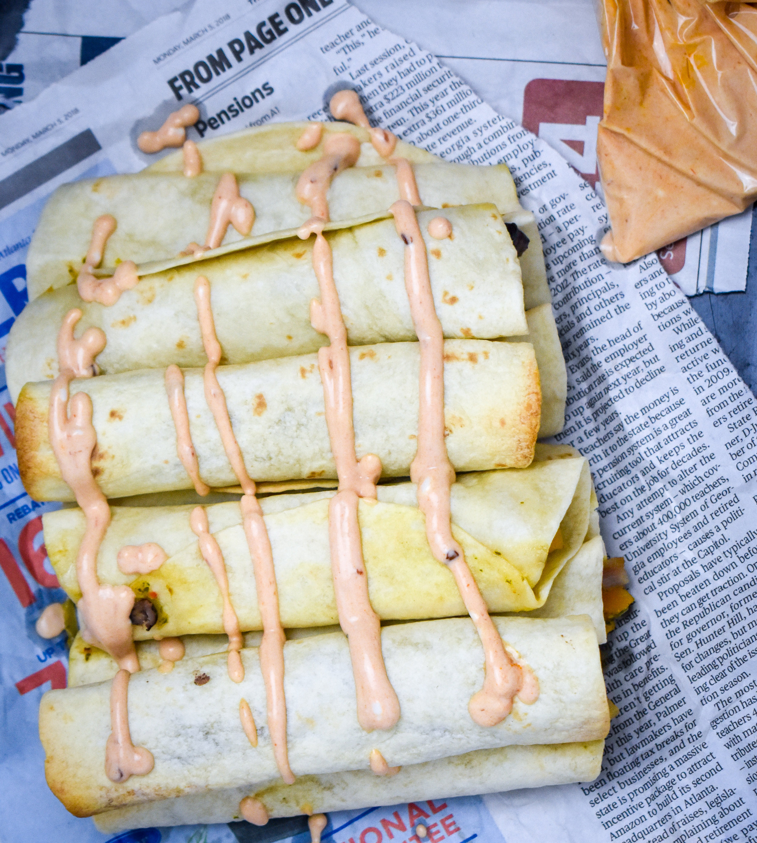 7. Once the taquitos are done baking, remove carefully with a spatula and line up on a plate. You can use the aioli as a dipping sauce or you can drizzle it on. To do this, snip off a corner of a ziploc bag filled with the aioli and squeeze on the aioli.