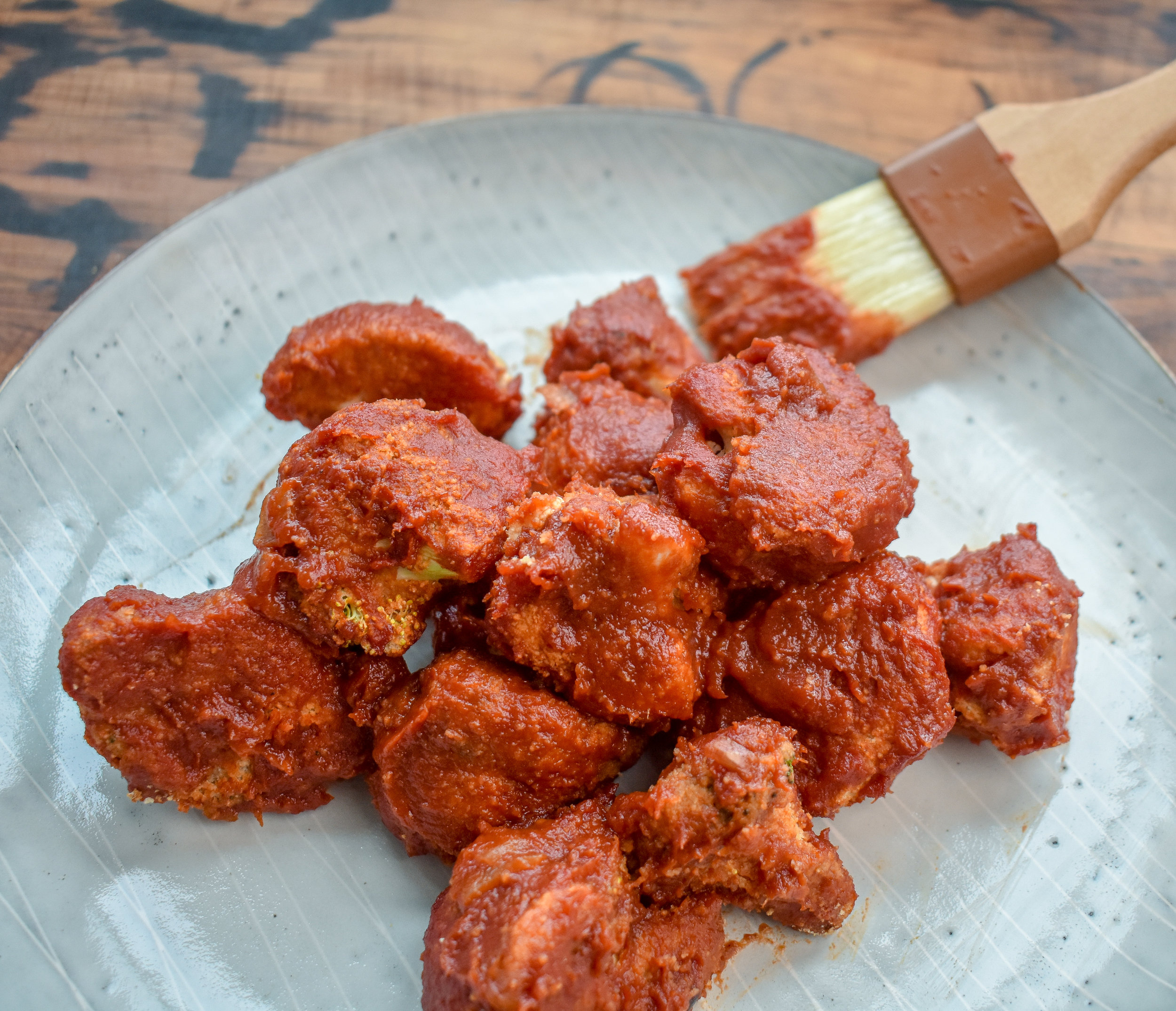 10. After the second bake, use the brush to coat on a bit more of the BBQ sauce to make them extra juicy + sticky. Serve + eat!