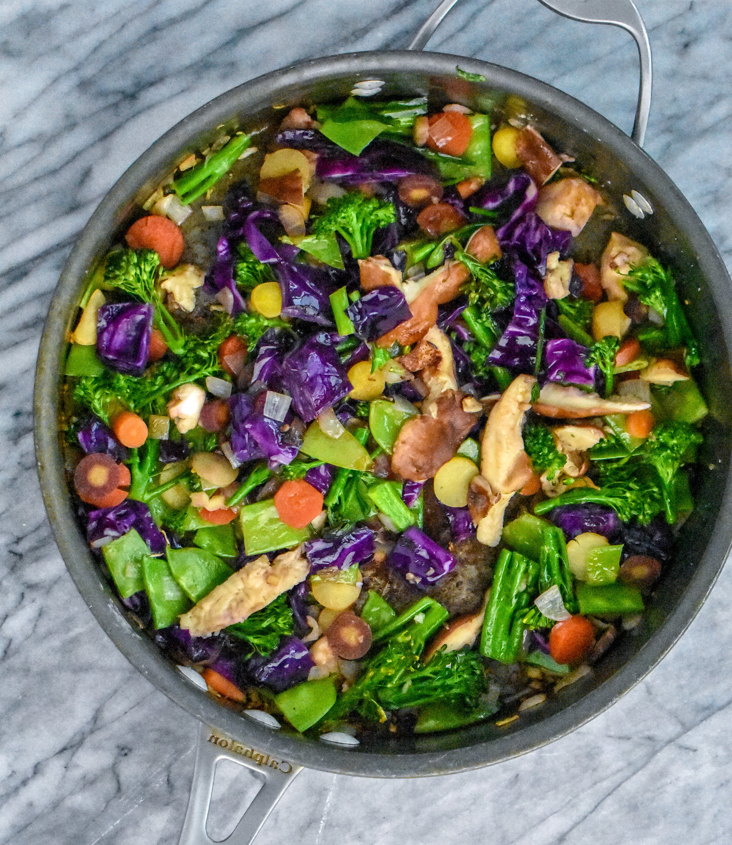 1. Add shallots, ginger, oil, and garlic to large frying pan. Cook for 4-5 minutes until the shallots have softened.Next, add in the cabbage. Cook for 60 seconds and then add the rest of the veggies. Cook for another 5-6 minutes. Add a pinch of salt + pepper. Set aside.