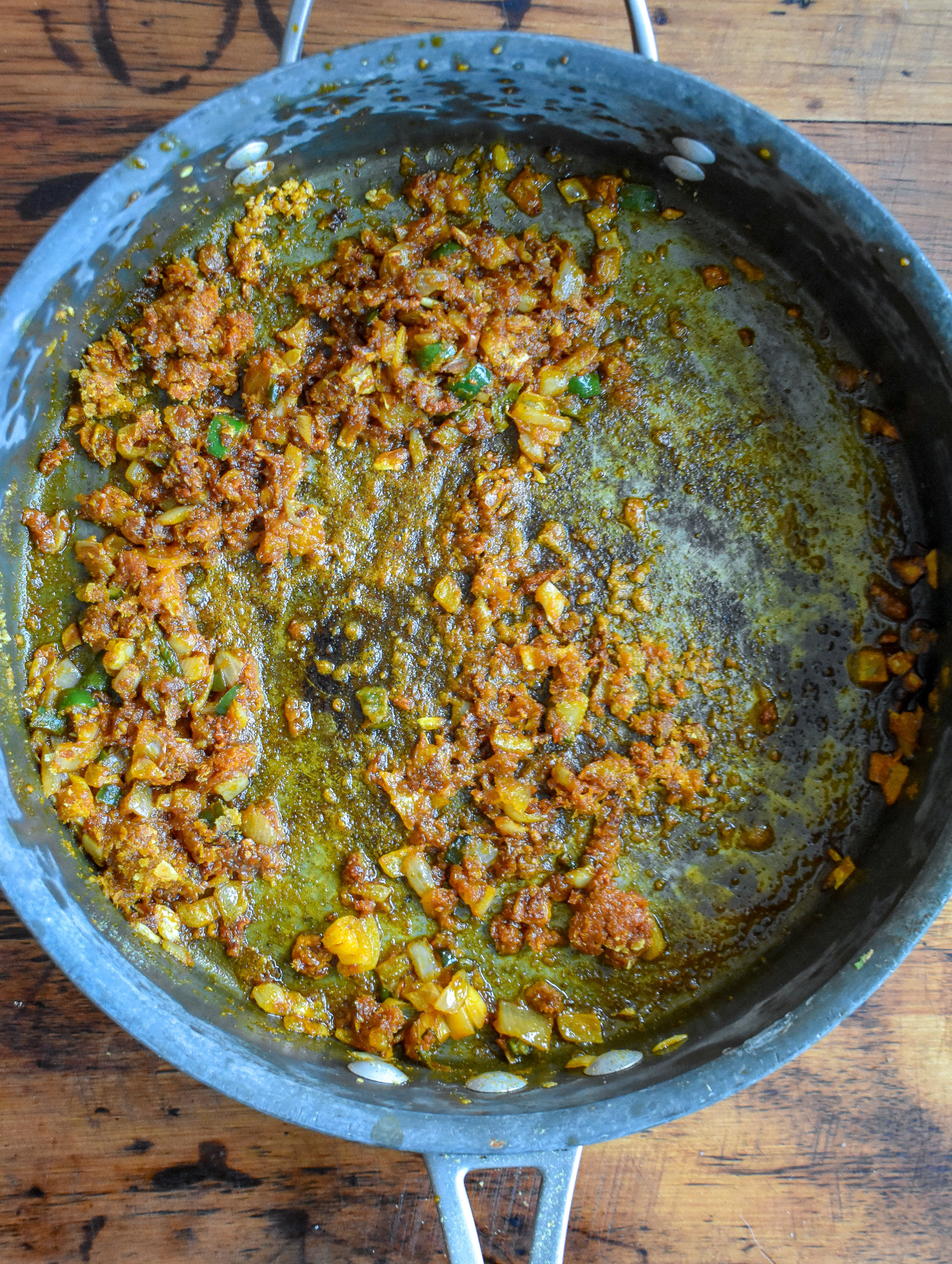 2. While the lentils cook, add palm oil to large frying pan and warm for 90 seconds. Add in onion, garlic, serrano and cook for another 3 minutes. Add in spices and coat well.