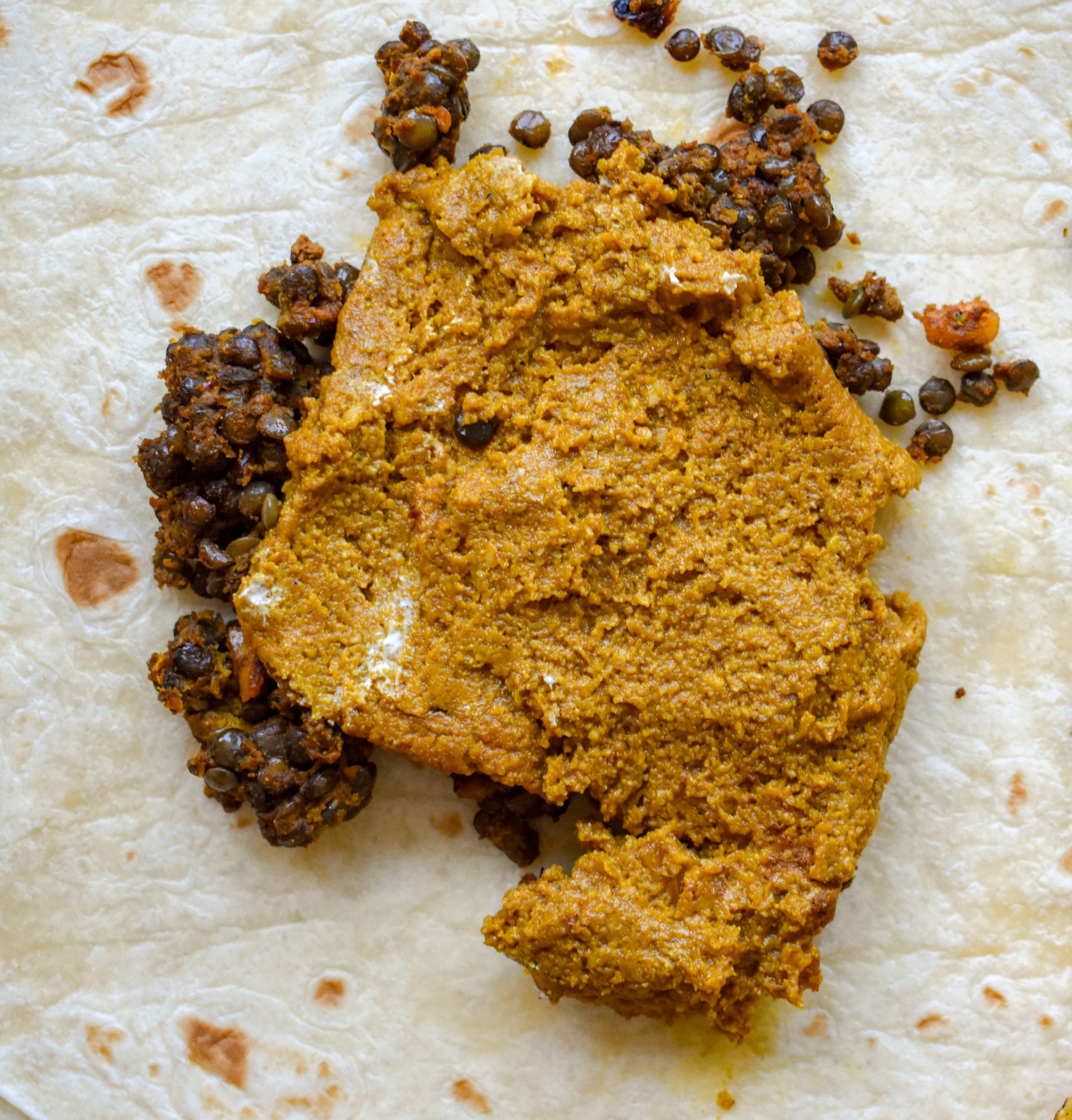 7. To construct, place 1/4 of the lentil meat recipe onto the extra large tortilla and then coat with a 1/2 cup of the cheese.