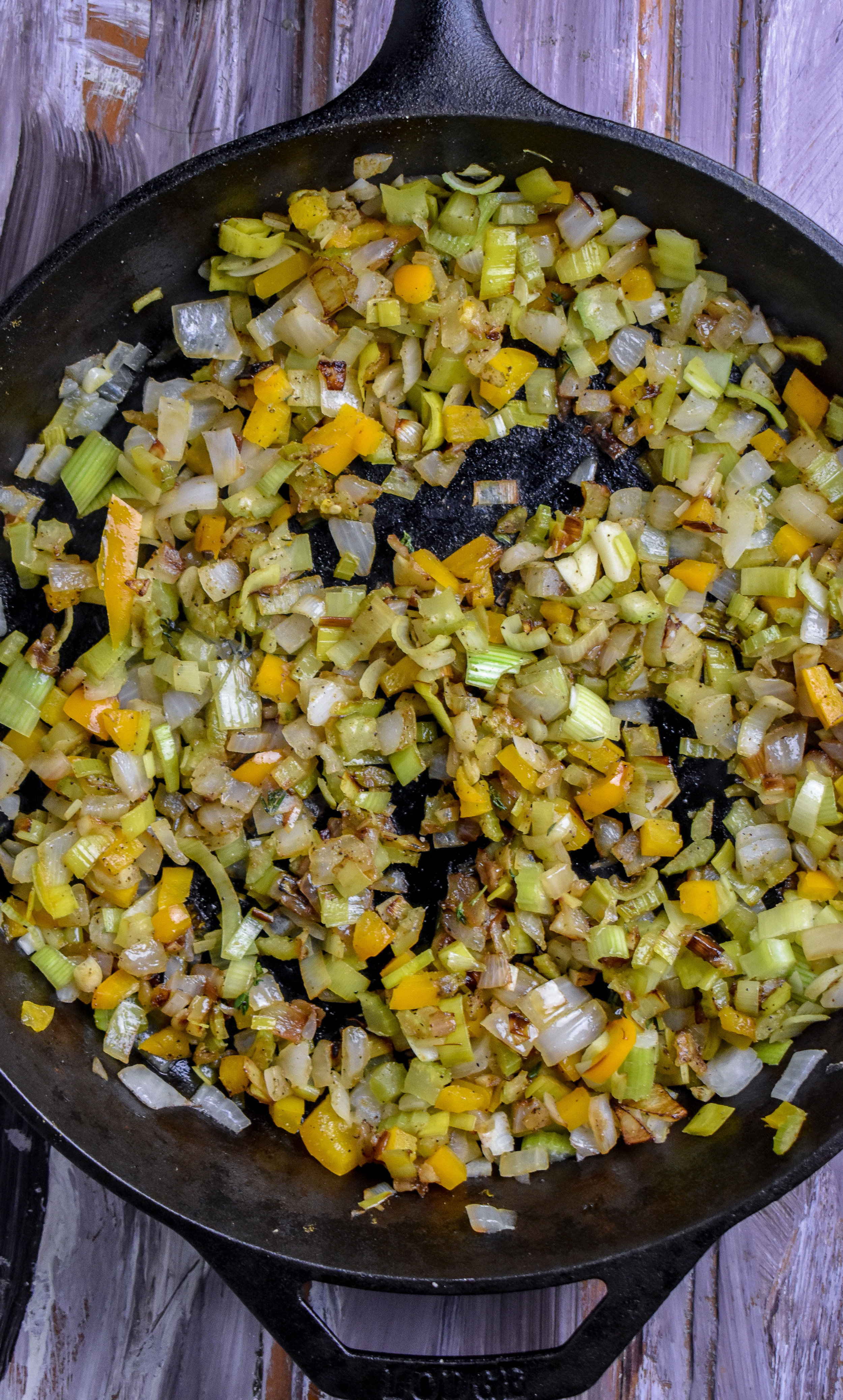 2. While rice cooks, add shallots + garlic to a castiron or large frying pan with poblano pepper or orange bell pepper (pictured above). Cook over medium heat for 2-3 minutes until onion starts to soften. Add in leeks + celery and cook another 5-6 minutes.