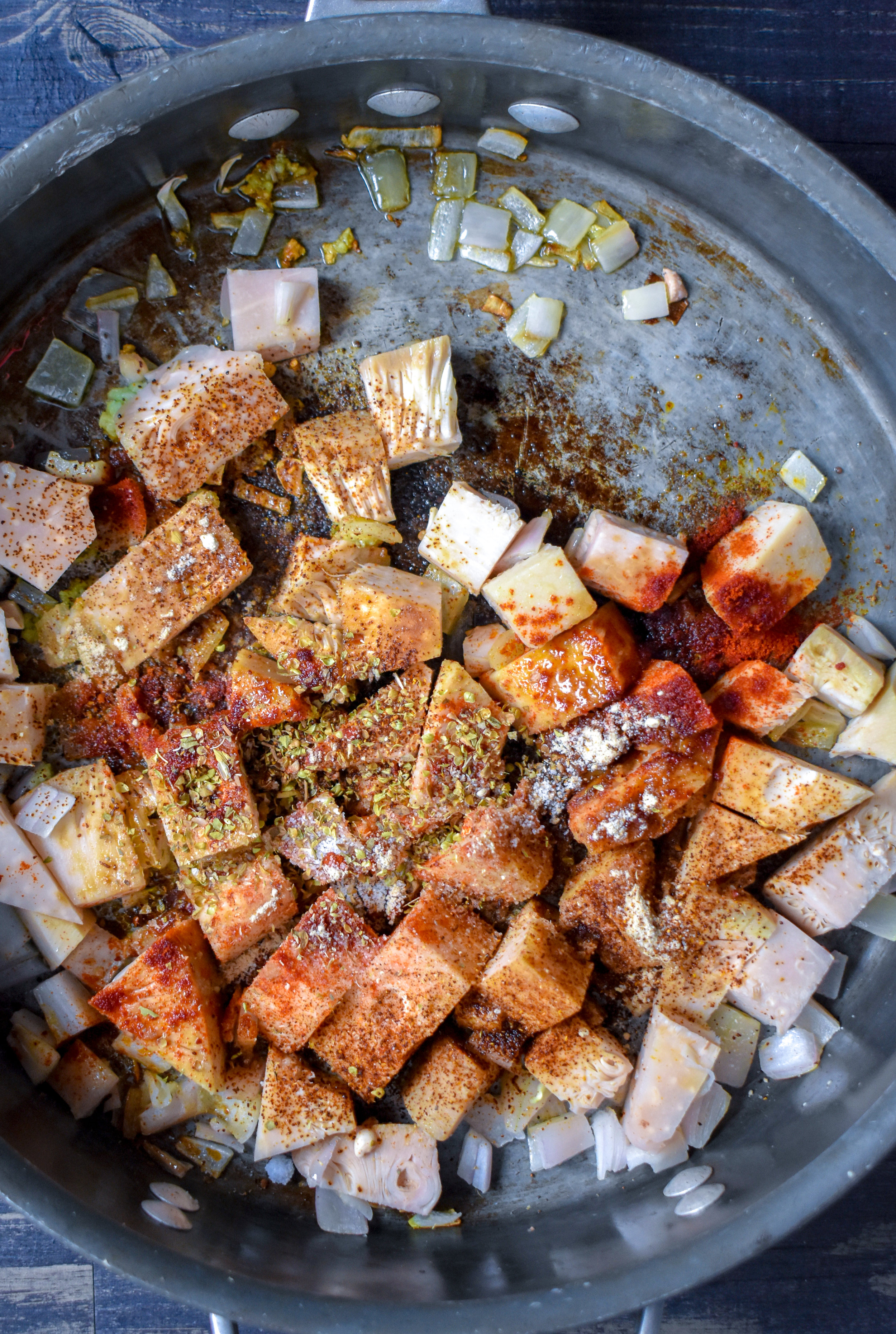 1. To start, add chopped shallot + garlic to pan with oil. Cook over medium heat for 5 minutes. Add diced jackfruit with BBQ seasoning, coat well, and cook for another 60 seconds.
